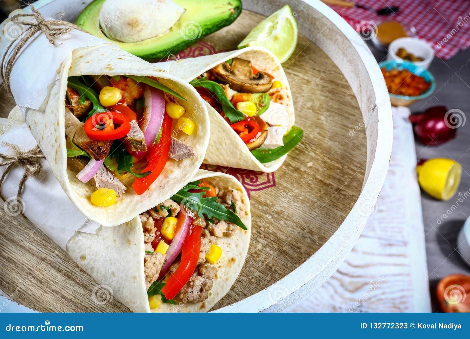 Burrito-, mexikan- och Tex-Mex mat, mjöltortilla med den fyllande closeupen för chili con carne på träskrivbordet