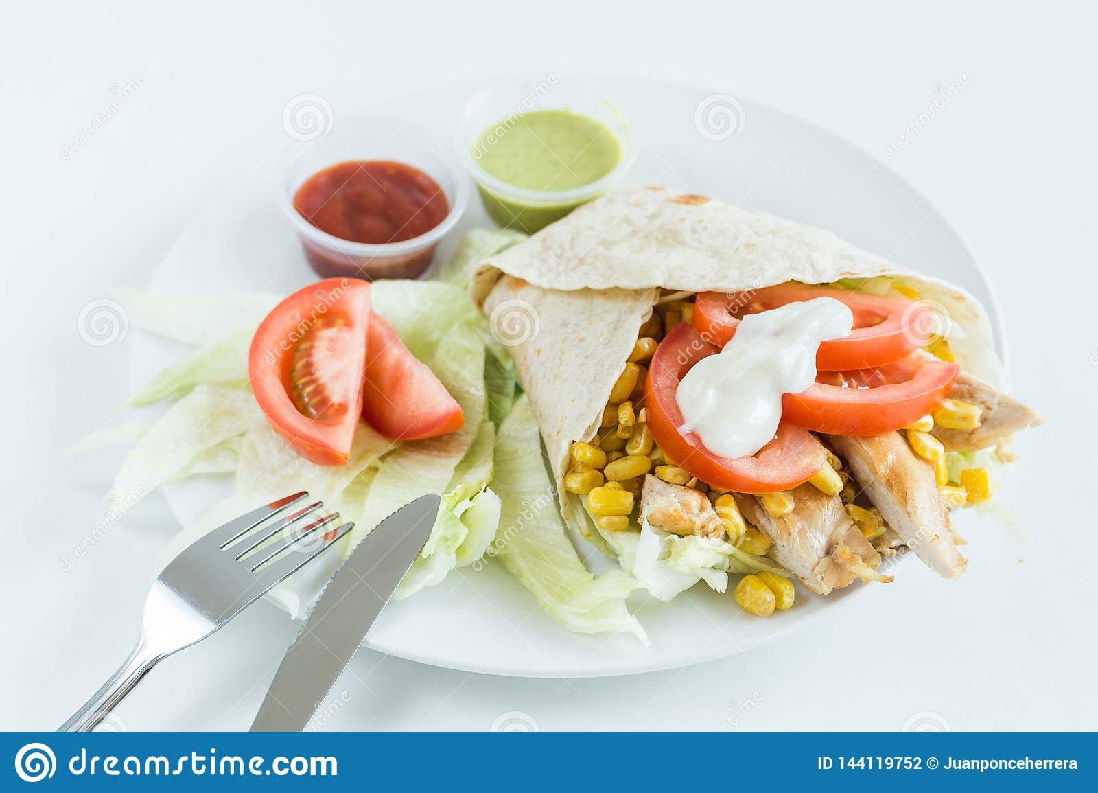 Burrito wrap with tomato, corn, lettuce, chicken, mayonnaise and sauces with white background
