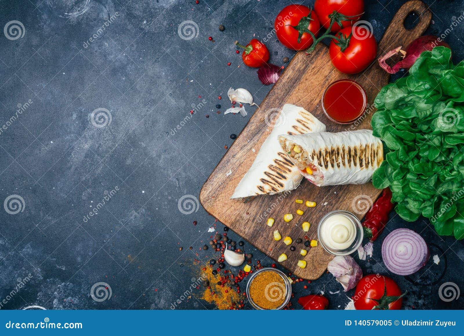 Burritosomslagen met geroosterde vlees en groenten - peper, tomaten en graan
