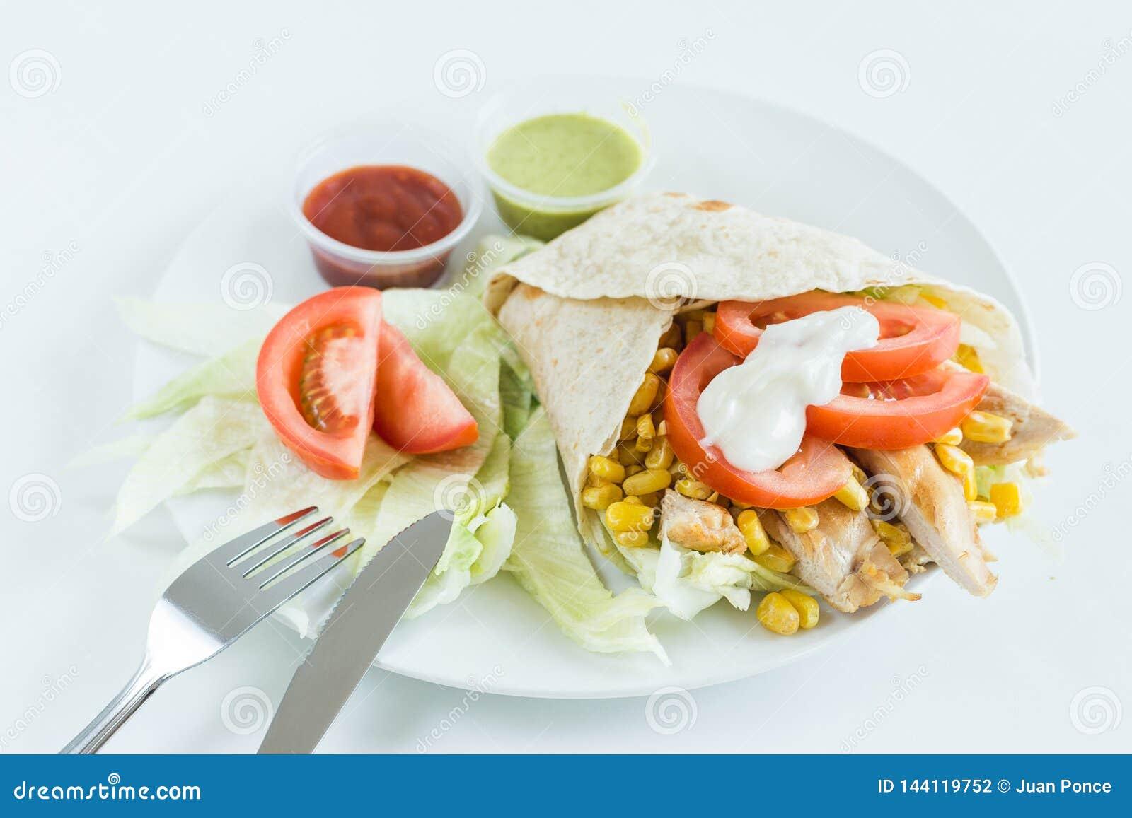 Burritoverpackung mit Tomate, Mais, Kopfsalat, Huhn, Mayonnaise und Soßen mit weißem Hintergrund