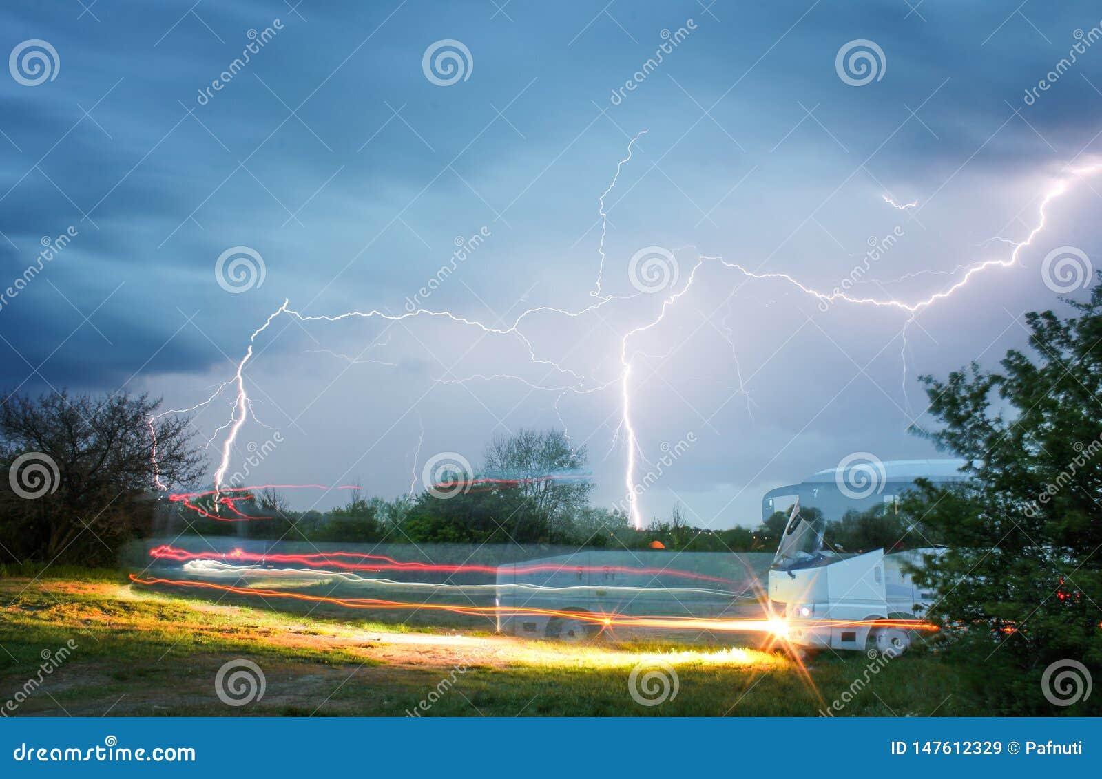 Bus nella campagna che guida contro il contesto di un cielo e di un fulmine tempestosi