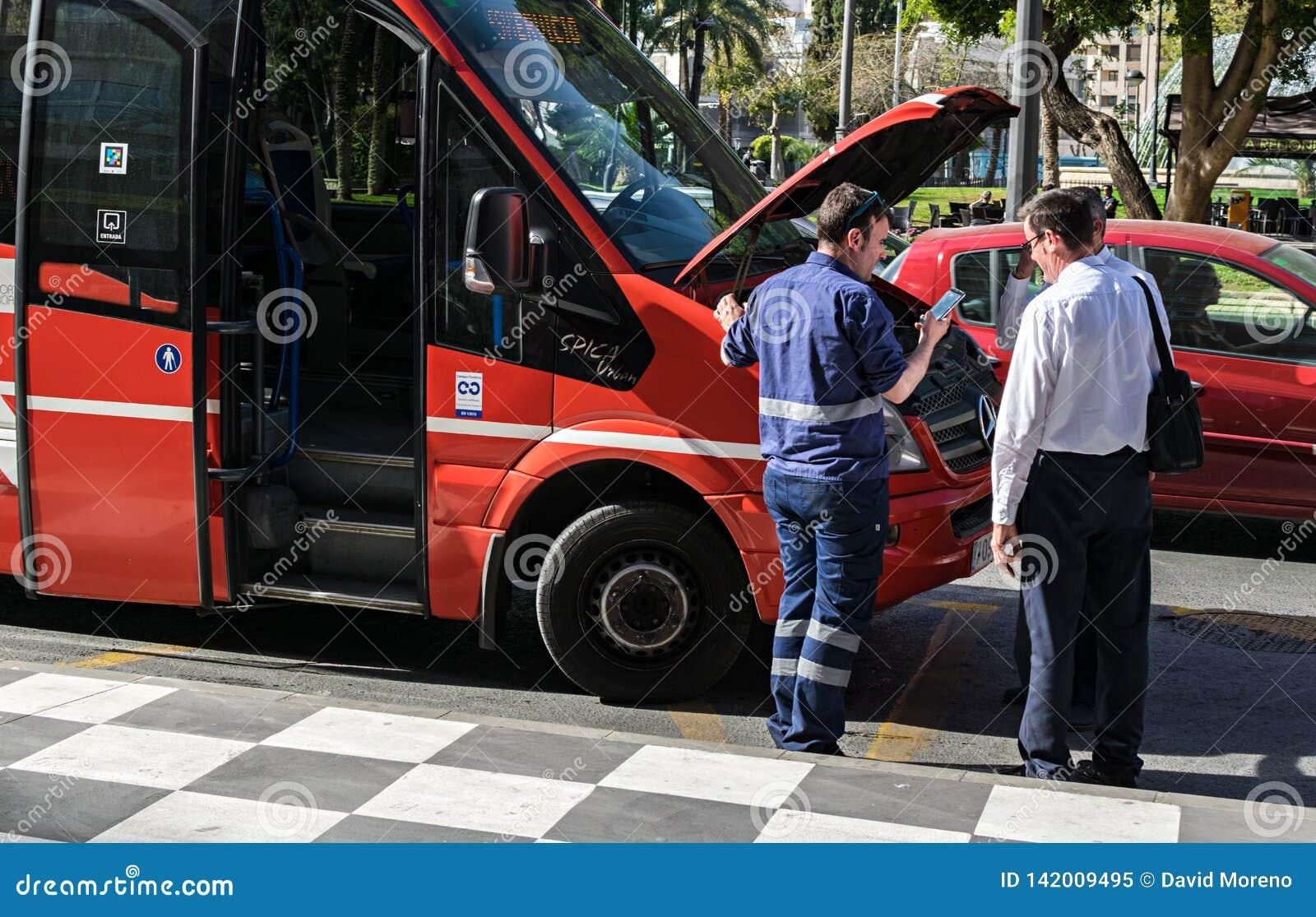 Buschauffeurs en werktuigkundige die terwijl de bonnet van de bus open is debatteren