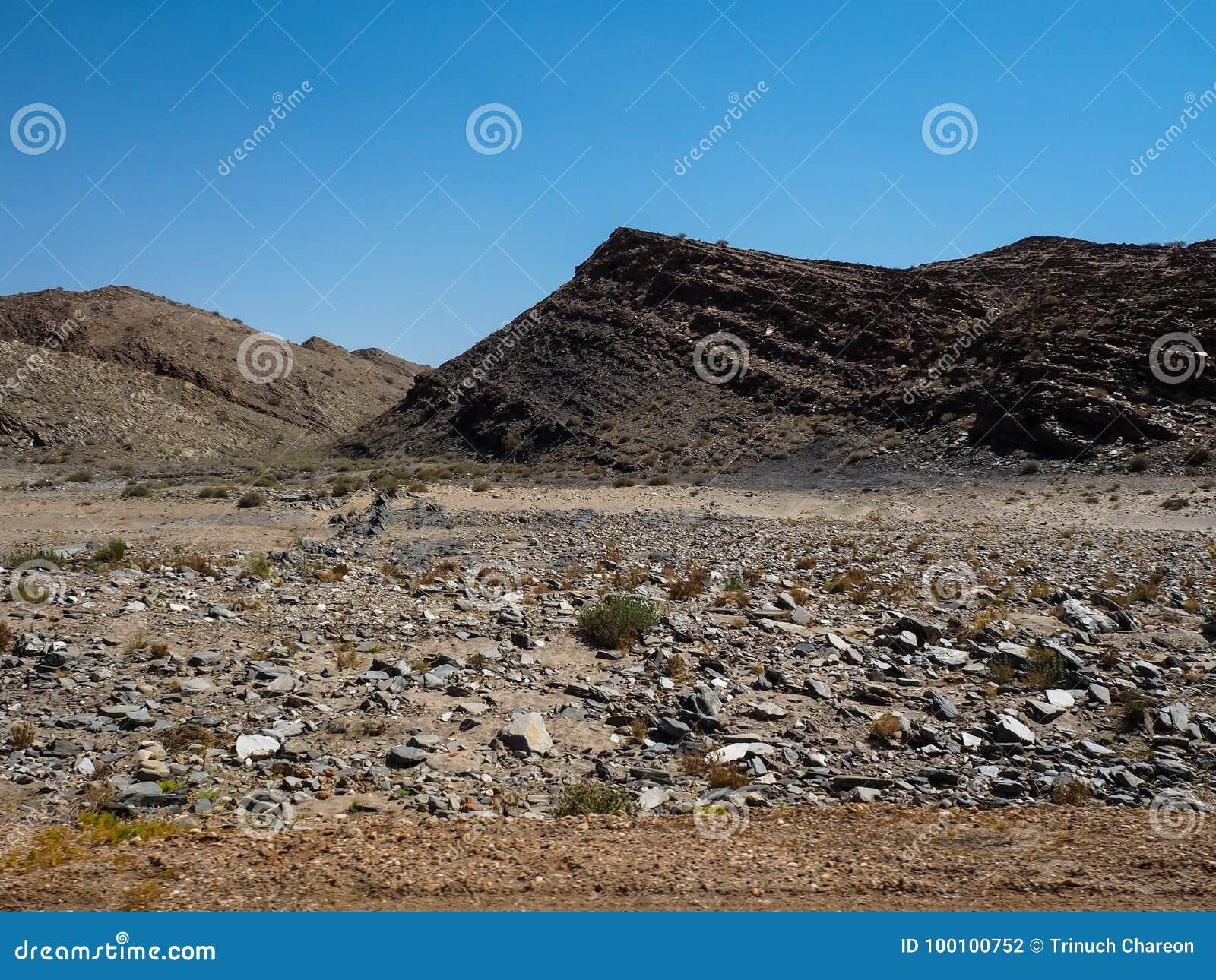 Busen vaggar jordning för bergtorkalandskapet av unik geografi för den Namib öknen med den blixtrande stenen och deserterar den g