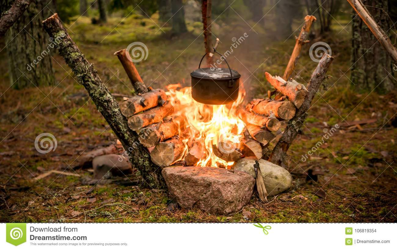 Bushcraft setting with a camping pot hanging over a burning fire.