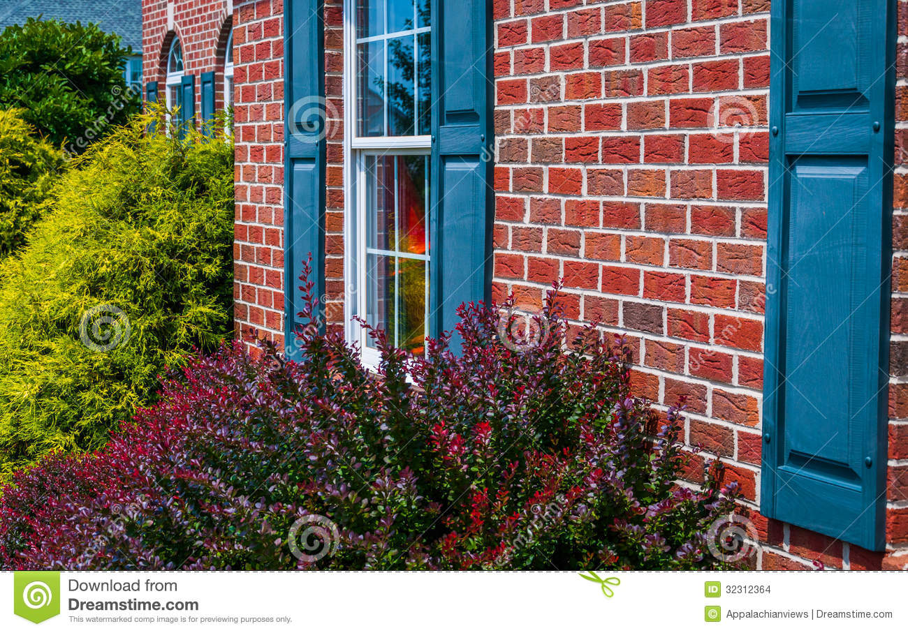 Bushes And Front Of Brick House With Blue Shutters Stock