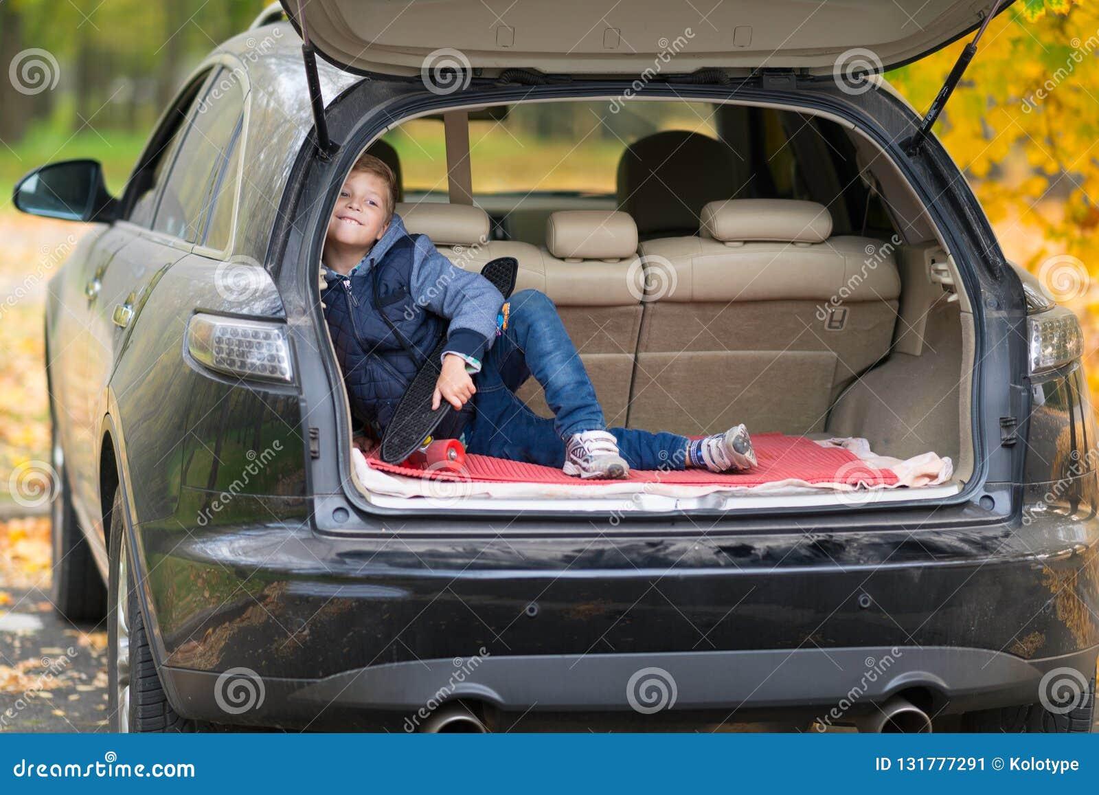 Busig pys med en skateboard som sitter i stammen av en bil som lyckligt utomhus grinar på kameran i en gata in