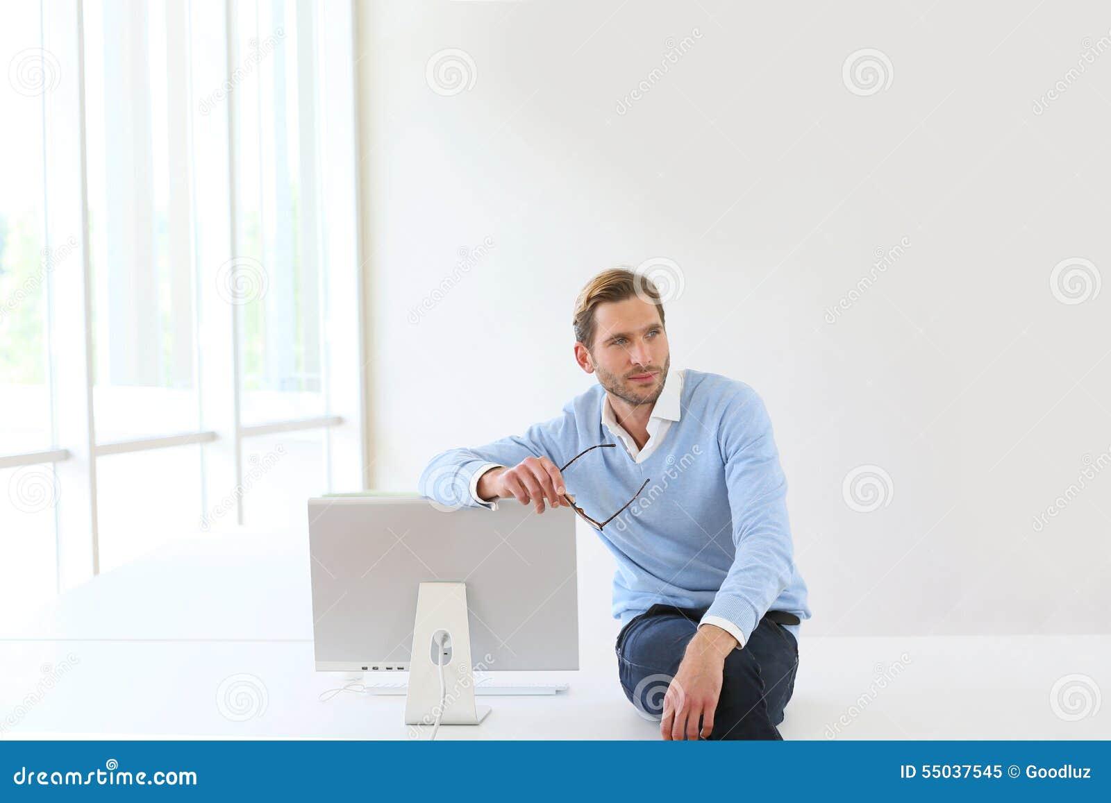 Busineesman, das auf dem Schreibtisch sich lehnt auf Monitor sitzt