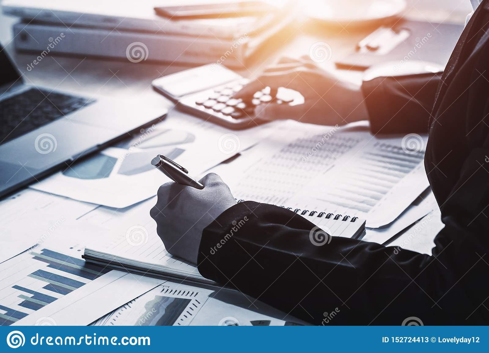 business accounting finance concept. accountant using calculator for calculate with laptop working in office