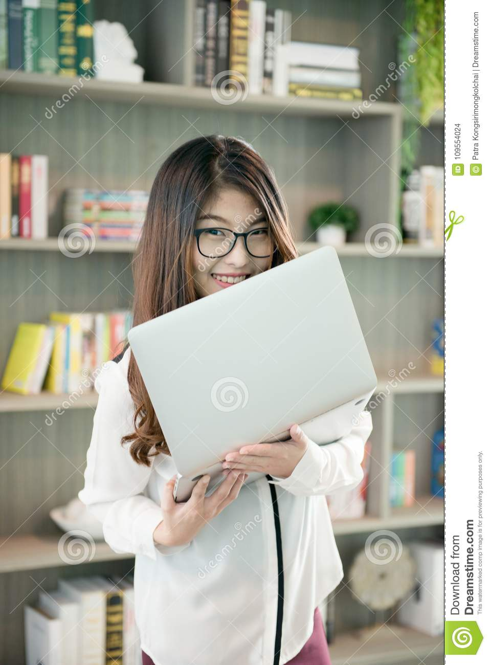 Business Asian woman holding a laptop in library