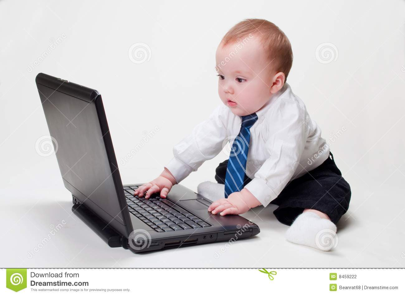 Cute baby businessman working on his laptop with a blank screen.
