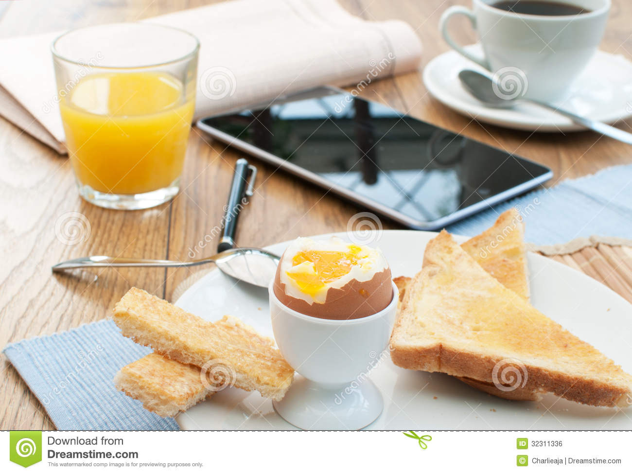 Table with breakfast and mobile tablet pen and newspaper