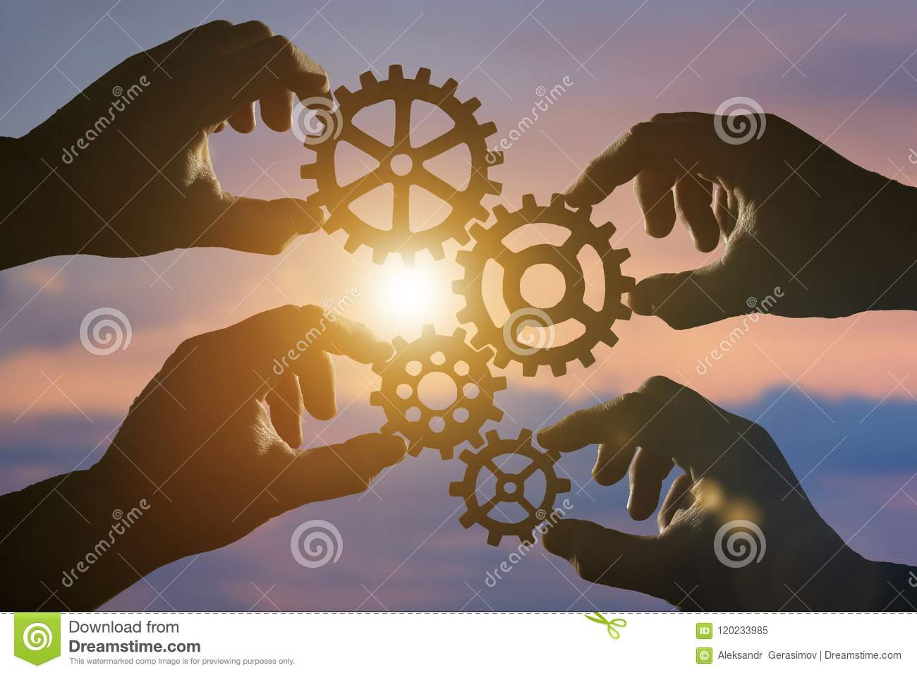 Business concept idea. four hands of businessmen collect a puzzle from gears.
