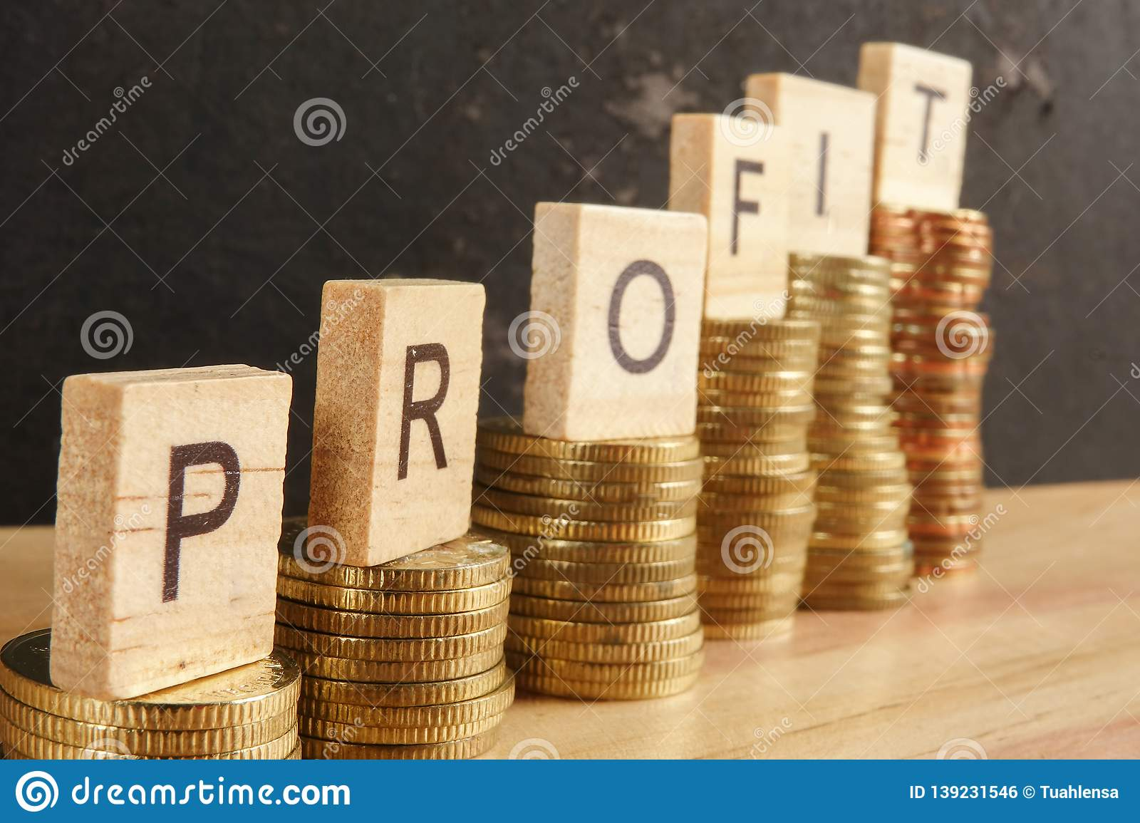 Business concept with PROFIT word on wooden plate onto hike trend stacked of coins.