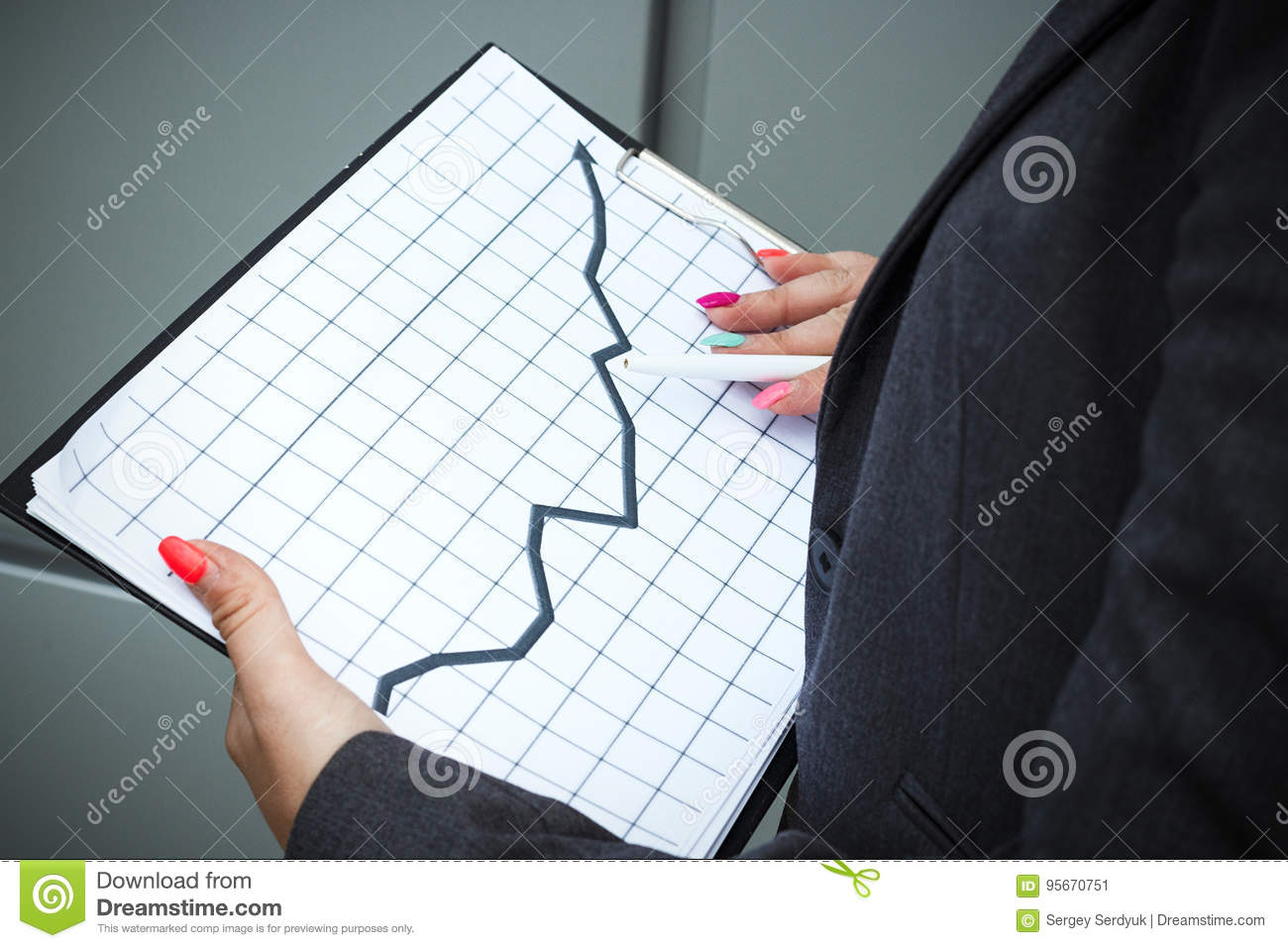 Business concept of success and growth. A successful woman boss, in a suit and wearing glasses, holds a tablet with charts