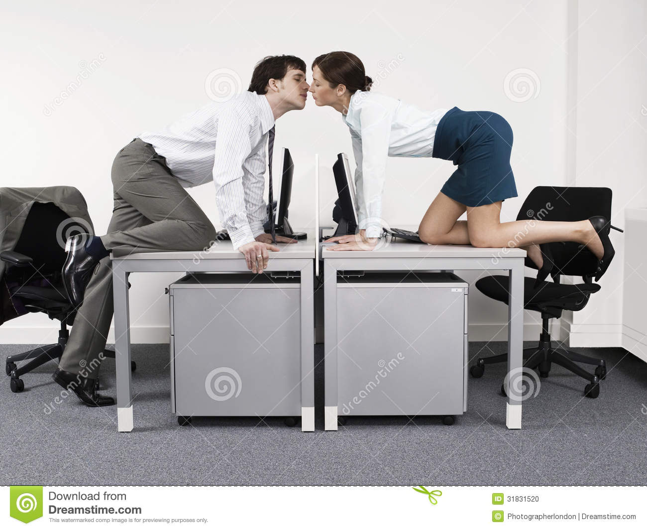Business Couple Kissing Over Desks In Office