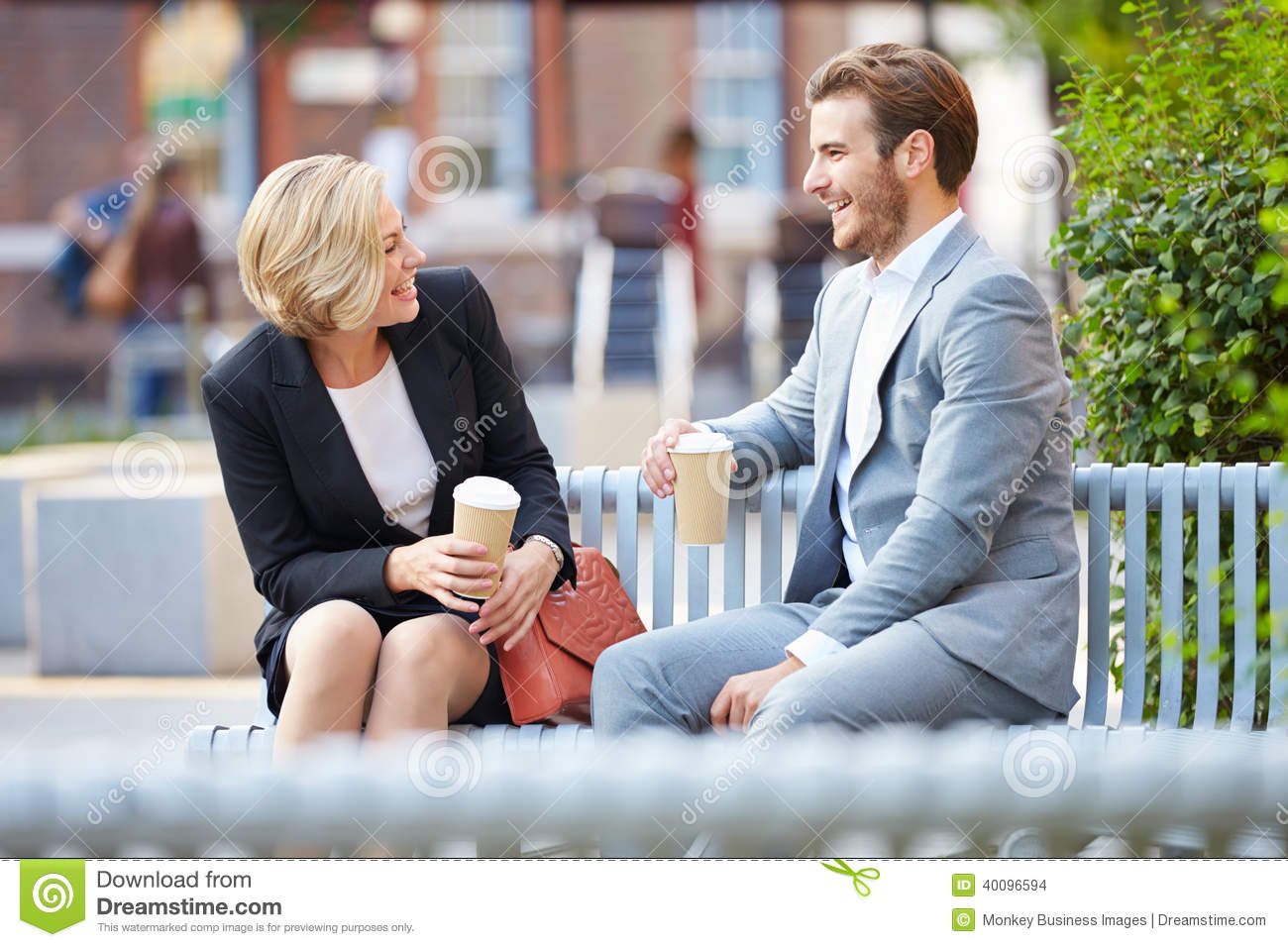 Business Couple On Park Bench With Coffee Stock Photo