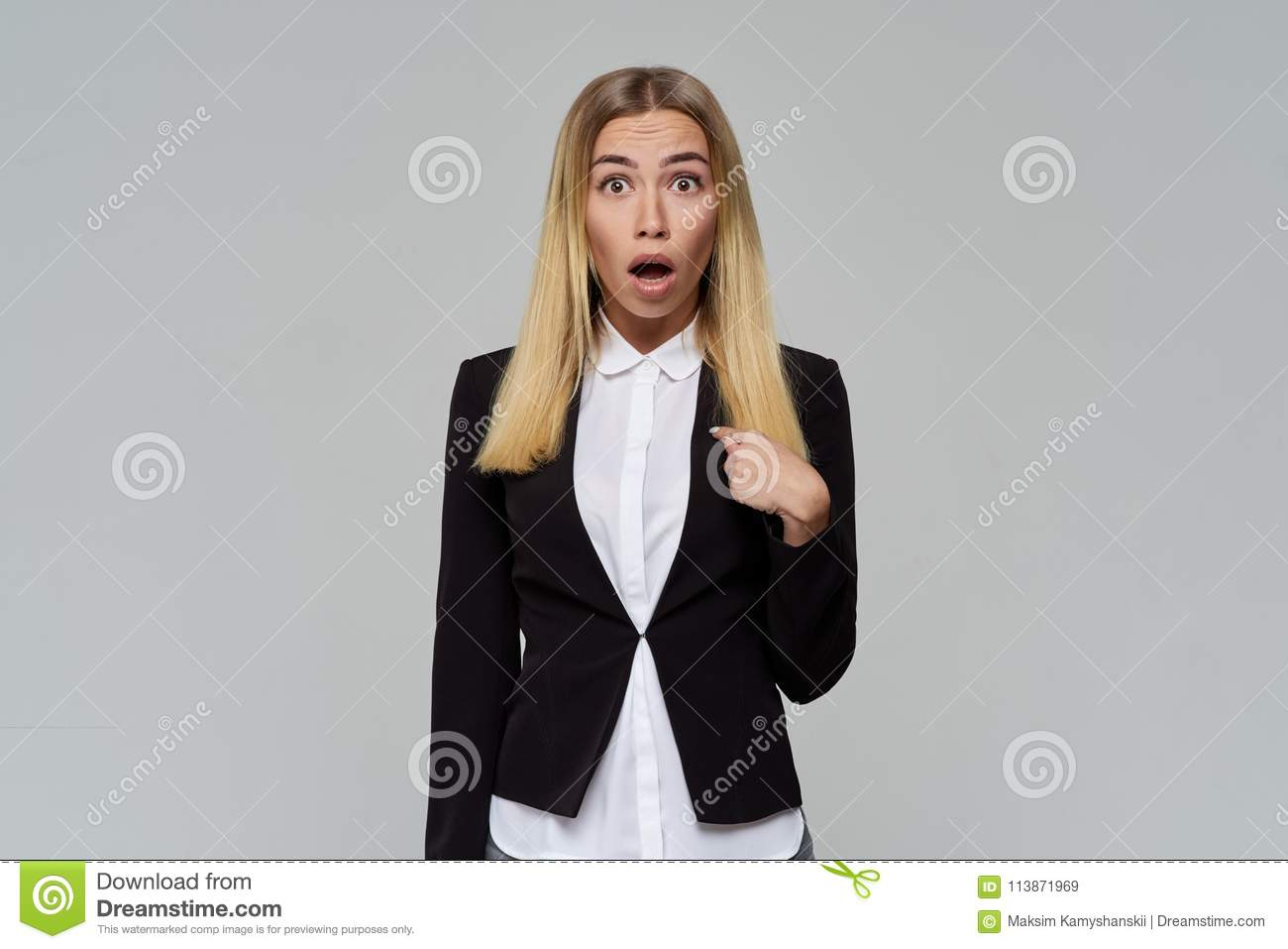 Business cute blonde woman with a shocked face opens her mouth and eyes wide in surprise and points at herself with her finger.