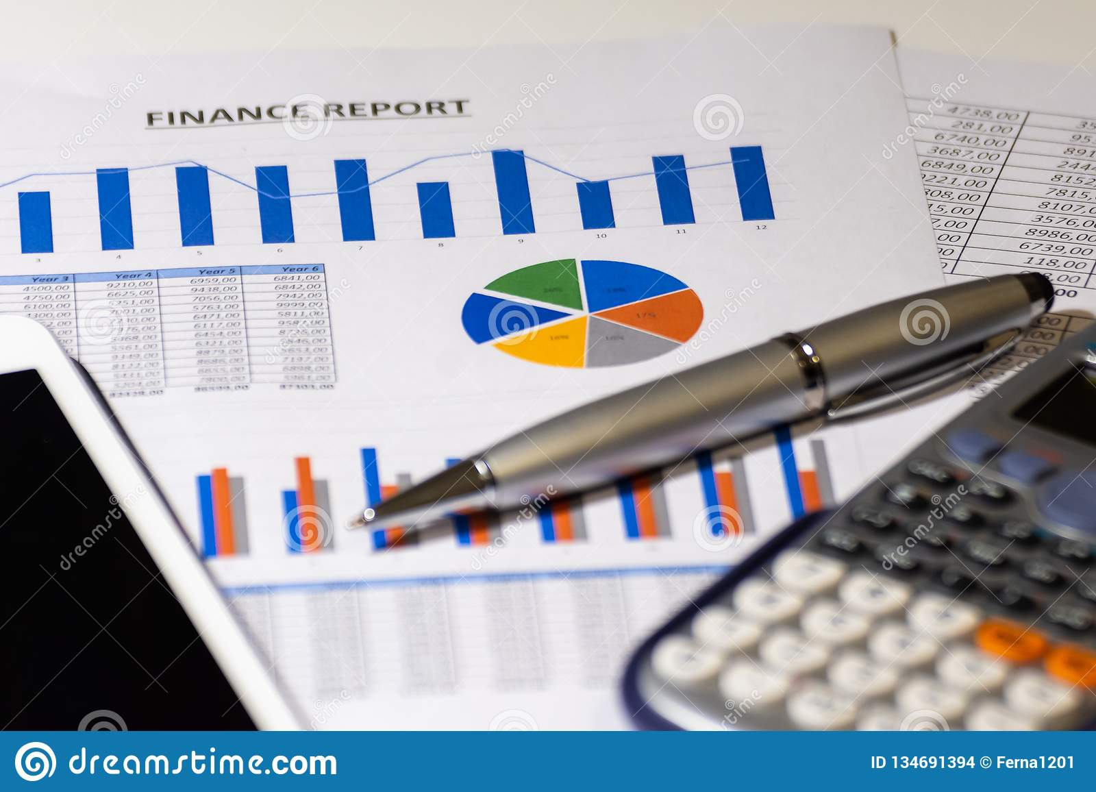 Business diagram on financial report with tablet, pen and calculator