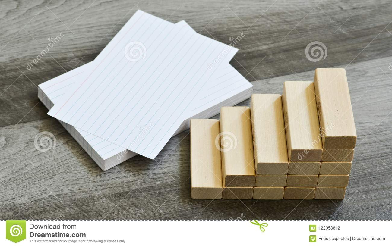 Business / Education Challenge Concept - Blank Index Cards With Stairway Upwards Of Building Blocks Over Dark Wooden Background