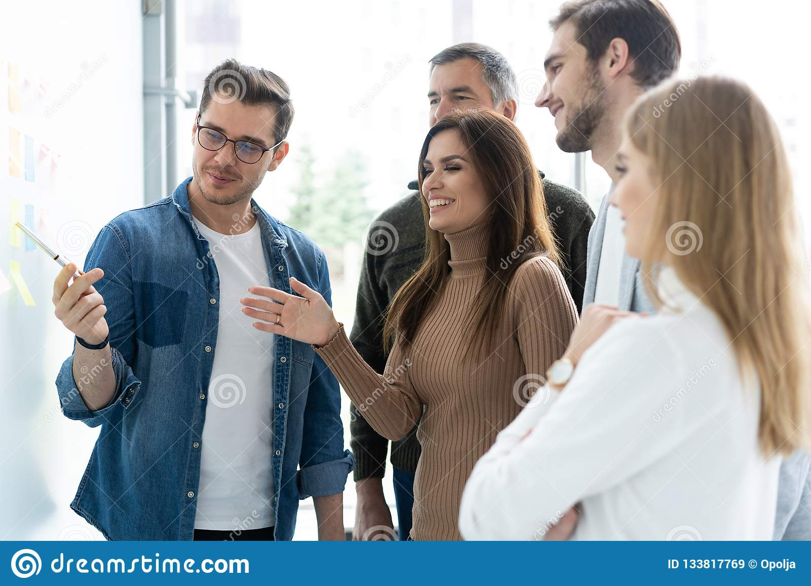 Business, education and office concept - business team with flip board in office discussing something.