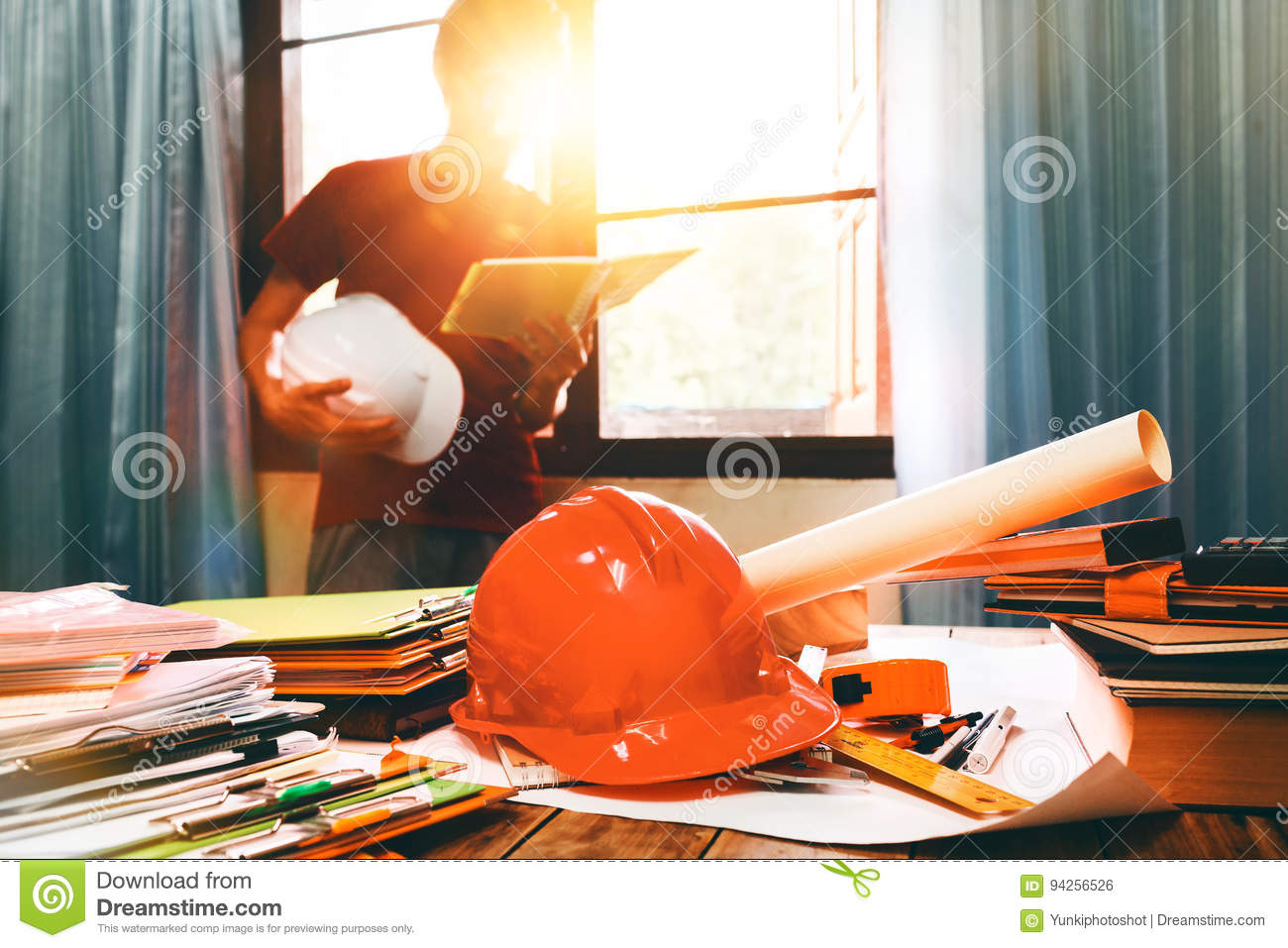 Business engineer working hard at his desk in apartment home building concept at construction site main office.