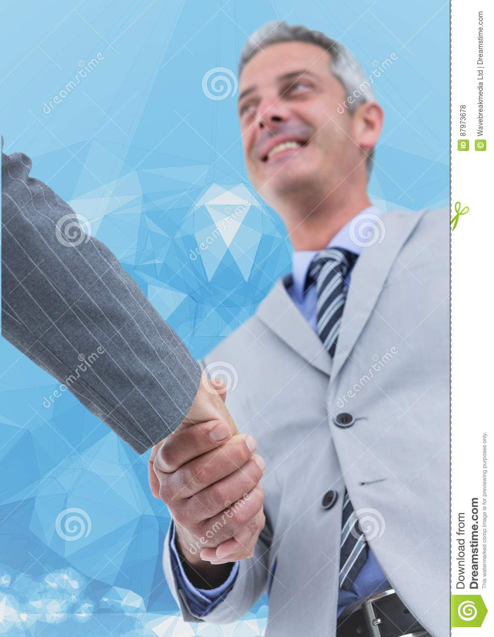 Business executives shaking hands against blue background