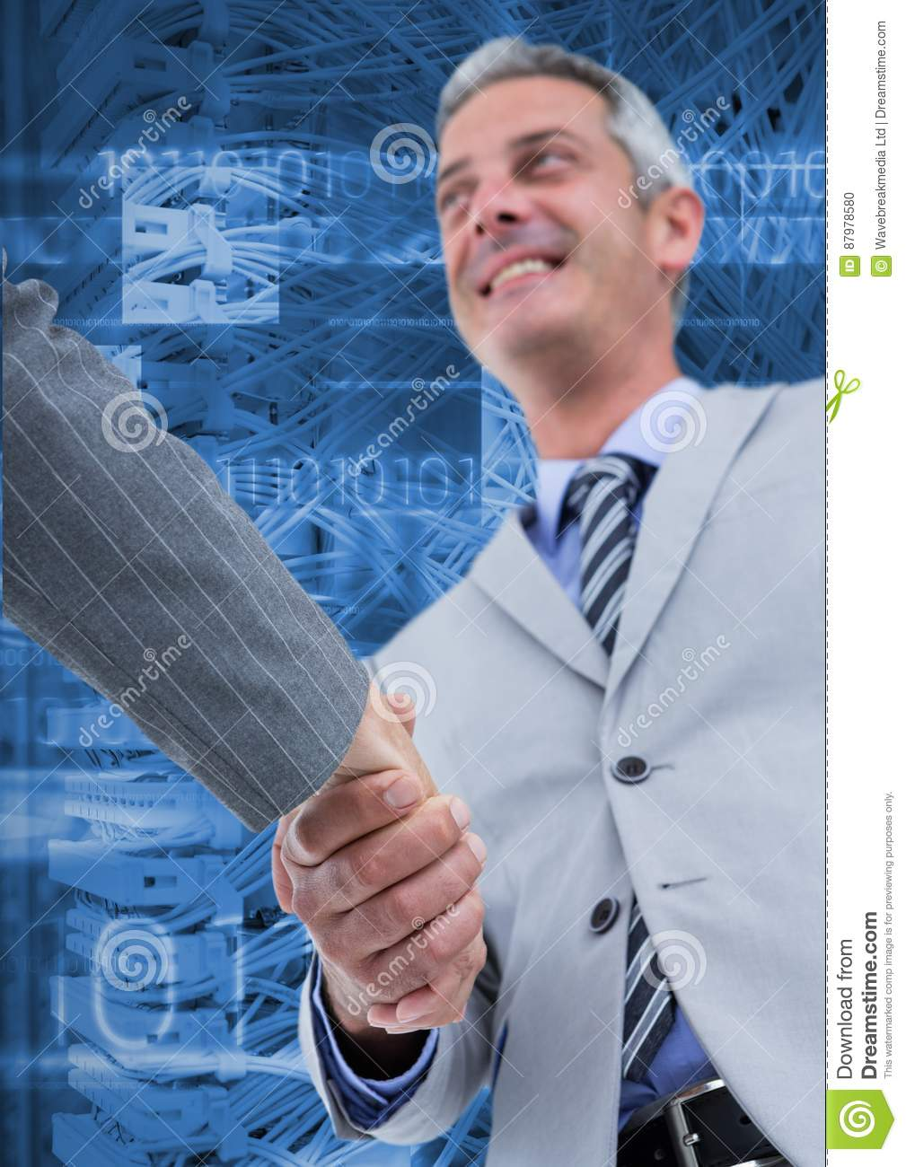 Business executives shaking hands against server systems in background