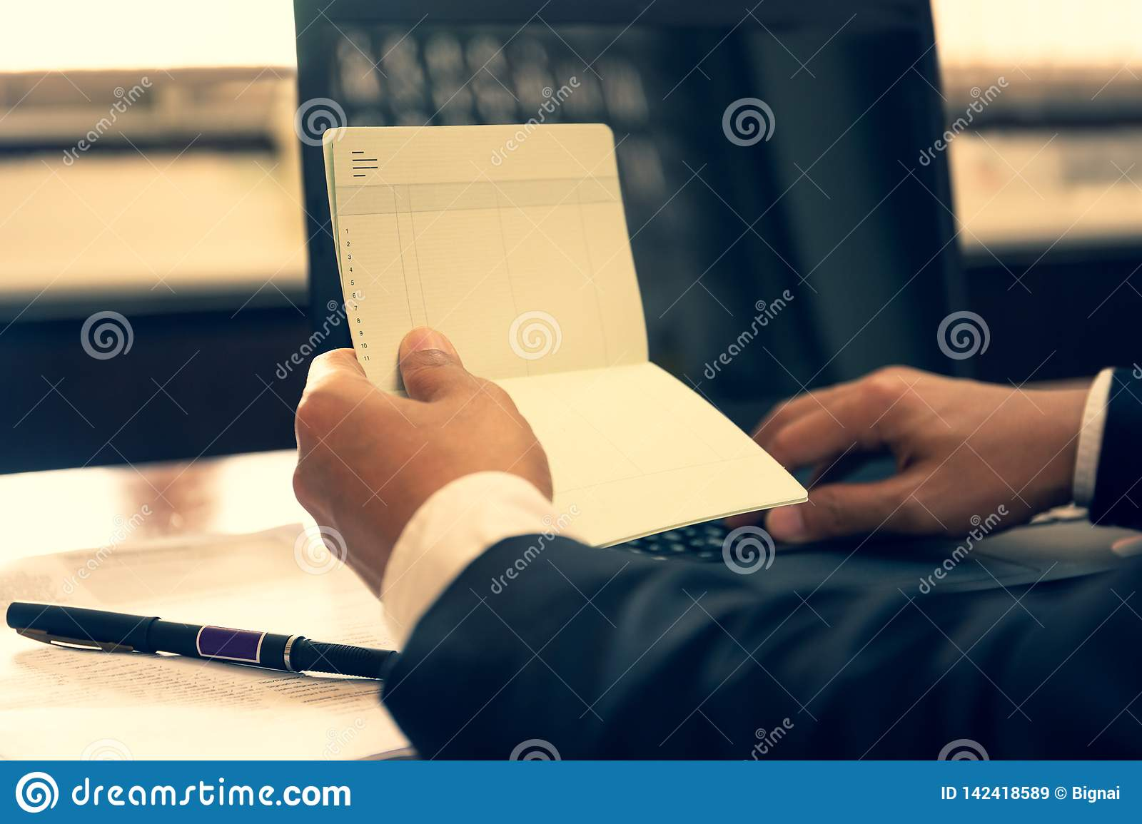 Business financial hand hold book statement and work with laptop.