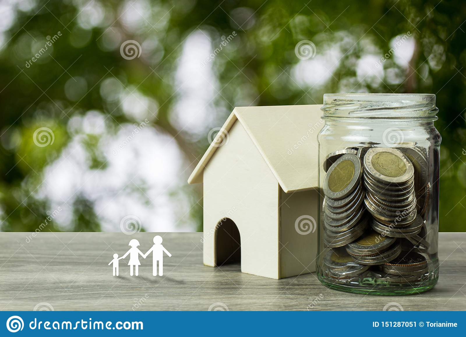Business and financial property concept for home loan, mortgage, saving and investment. A small house model with stack of coins in