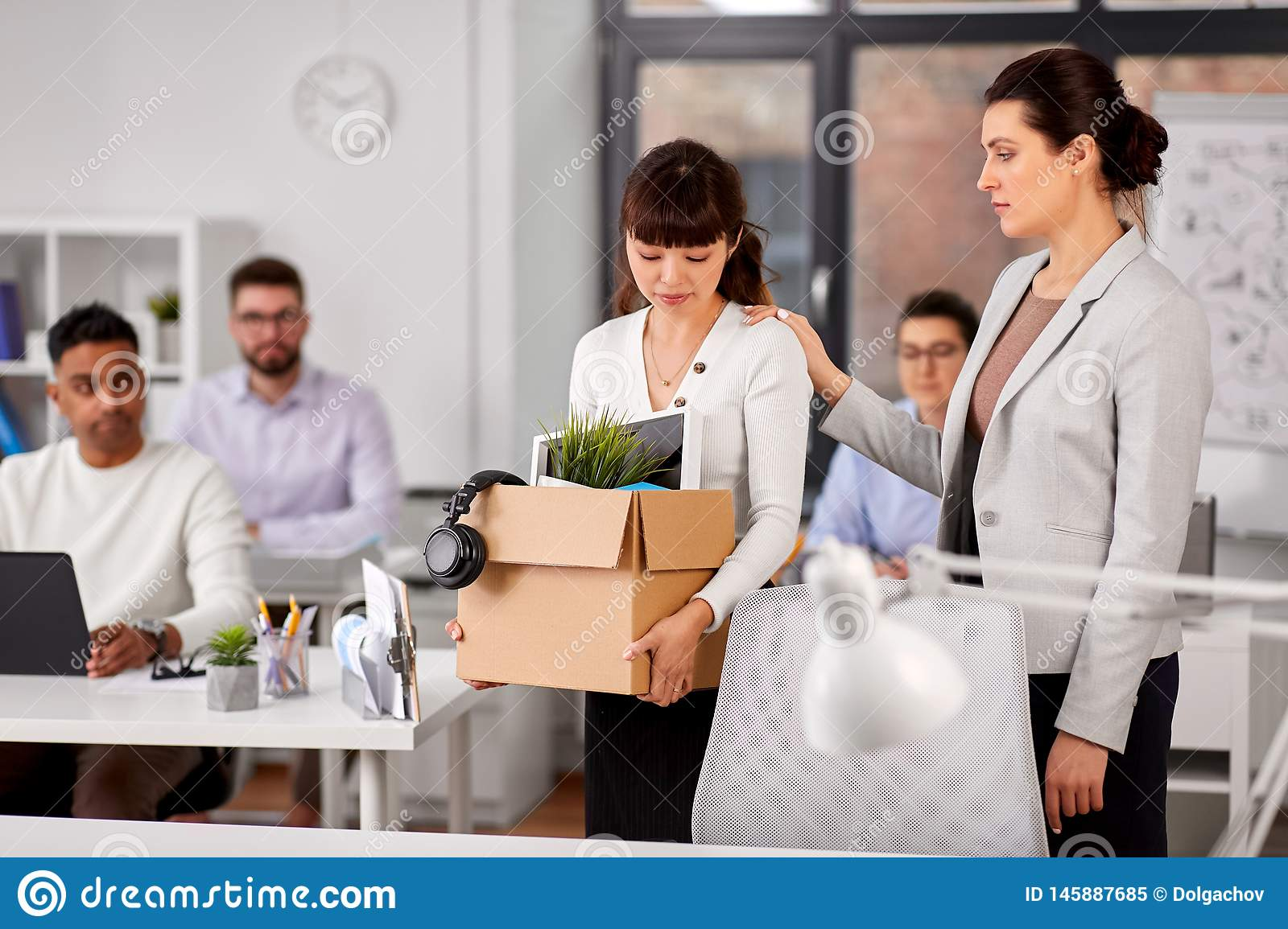 Colleague seeing off fired employee leaving office