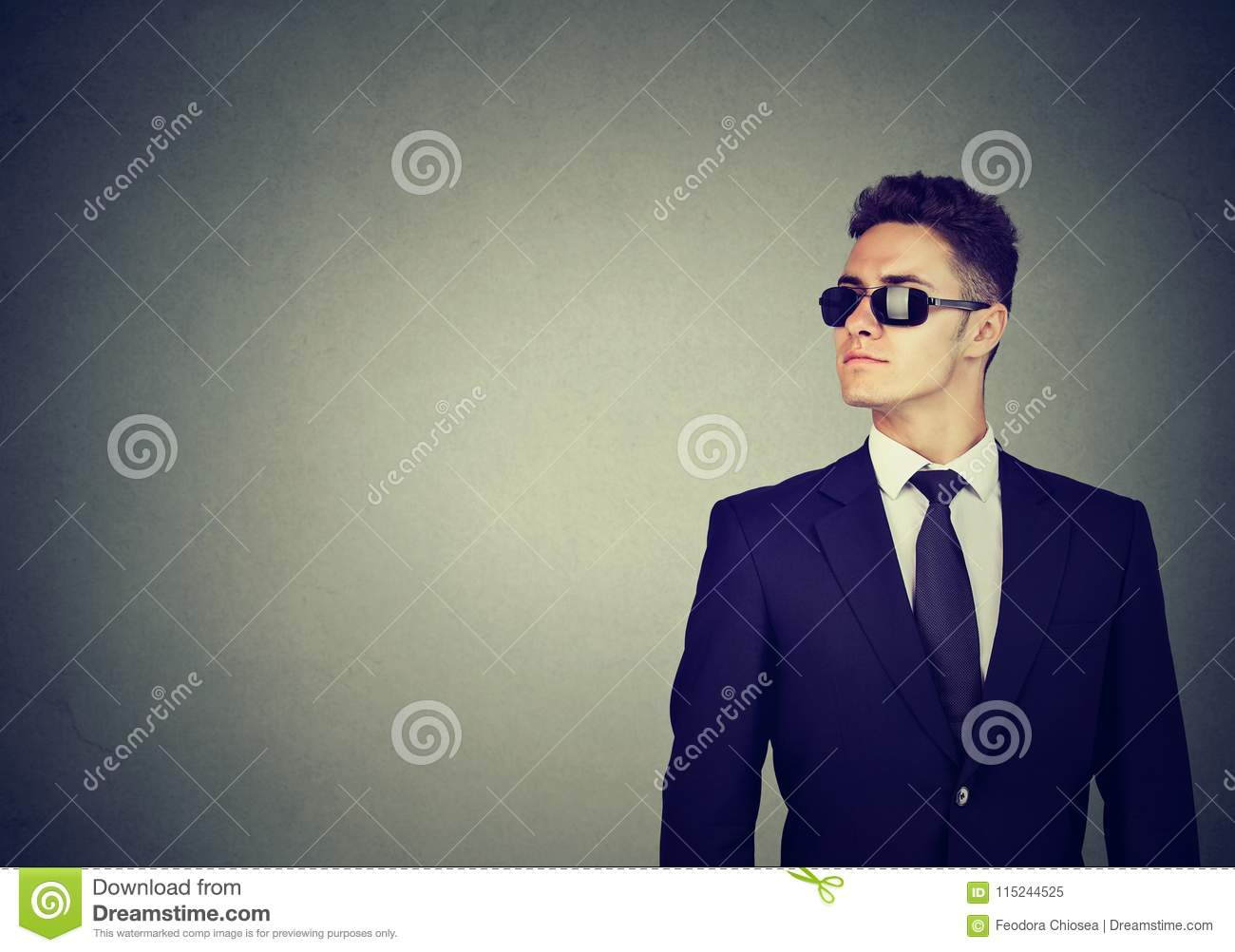 Business guy in sunglasses and suit on gray wall background