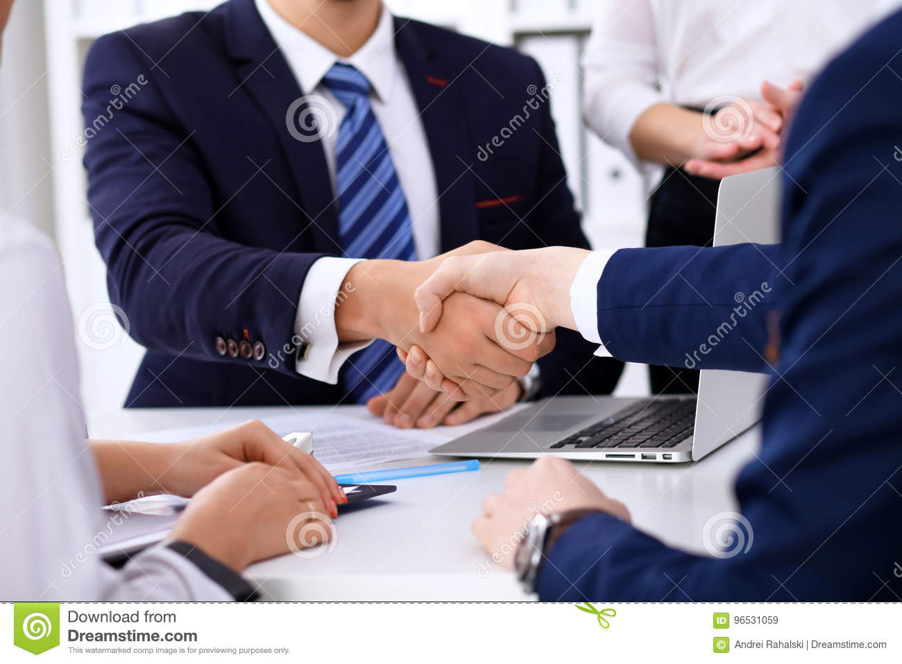 Business handshake at meeting or negotiation in the office. Partners are satisfied because signing contract or financial