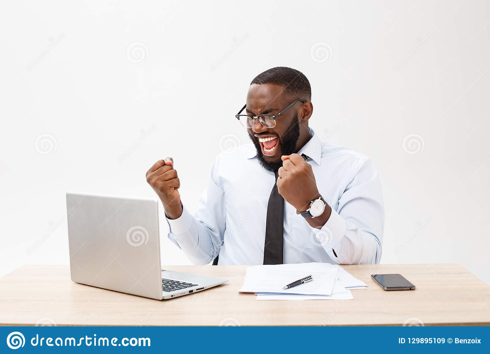 Business is his life. Cheerful young African man in formal wear and working on laptop