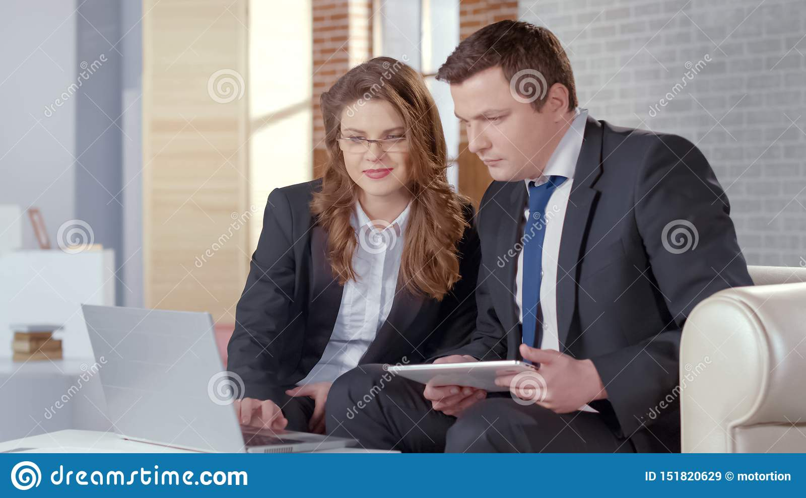 Business lady and man checking presentation on laptop, collaborate in business