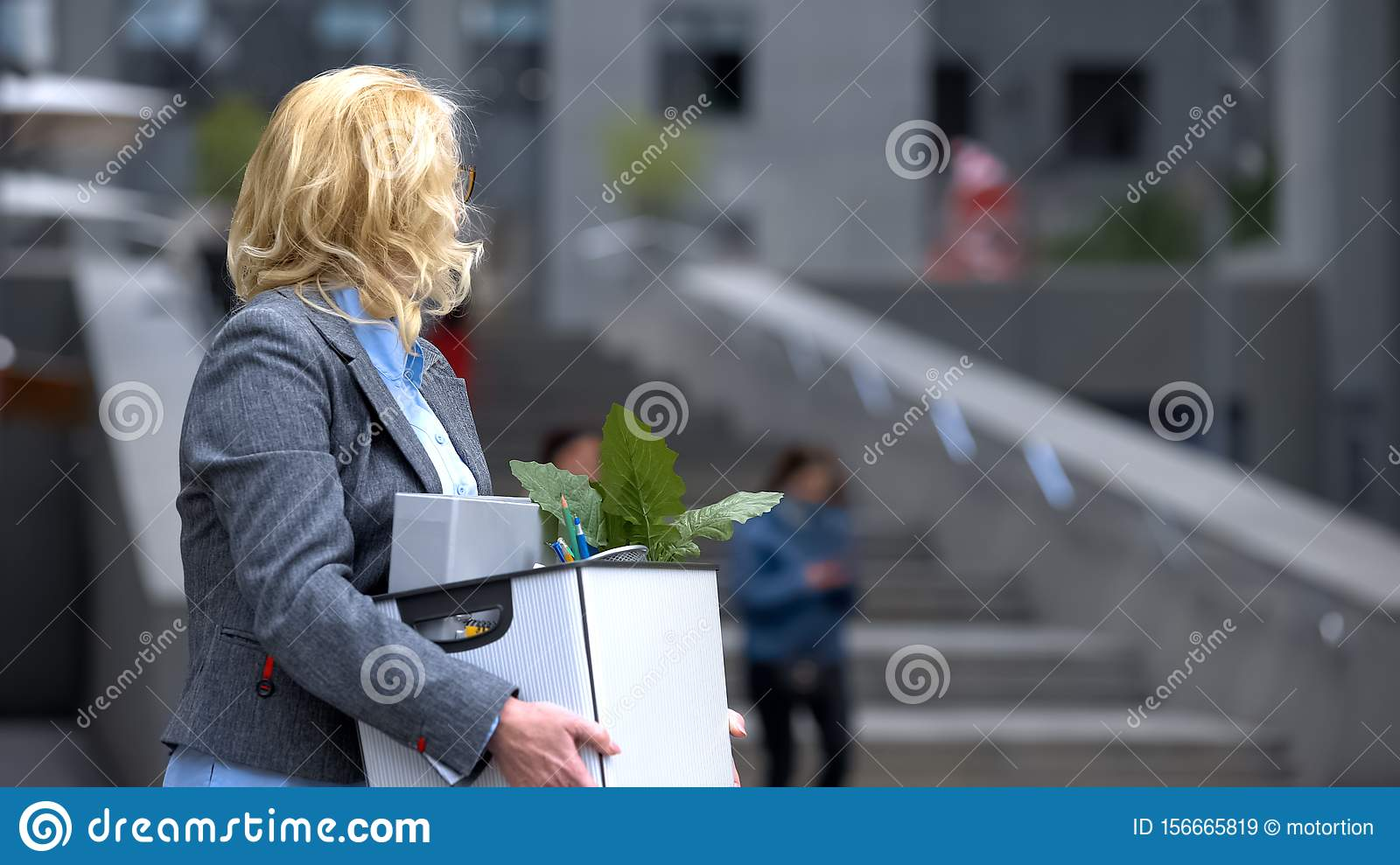 Business lady with stuff box looking at office building, pension unemployment