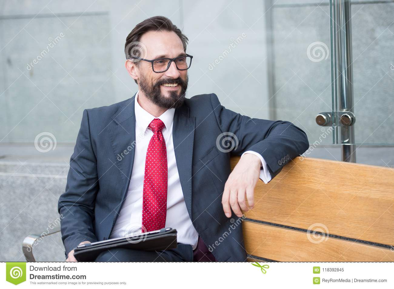 Business, Leisure, technology, communication and people concept-man with tablet on city street bench. Portrait of handsome man