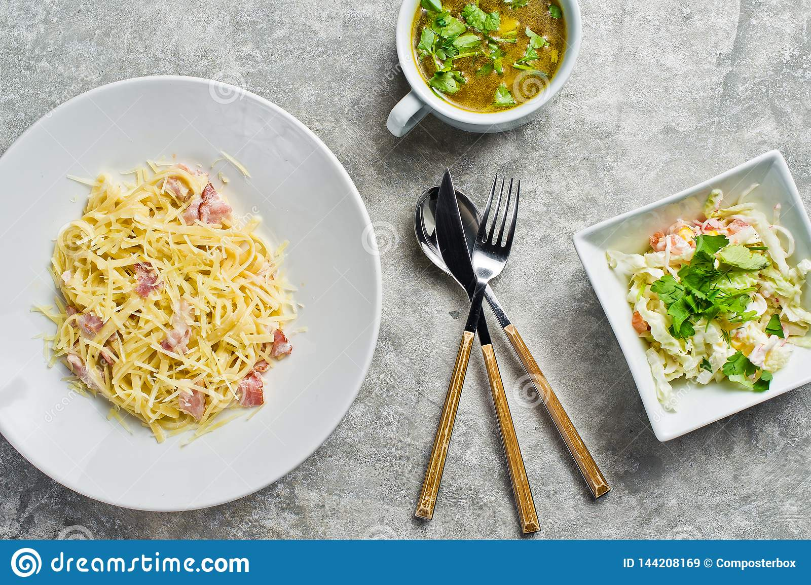 Business lunch menu, pasta Carbonara, green salad and chicken soup.