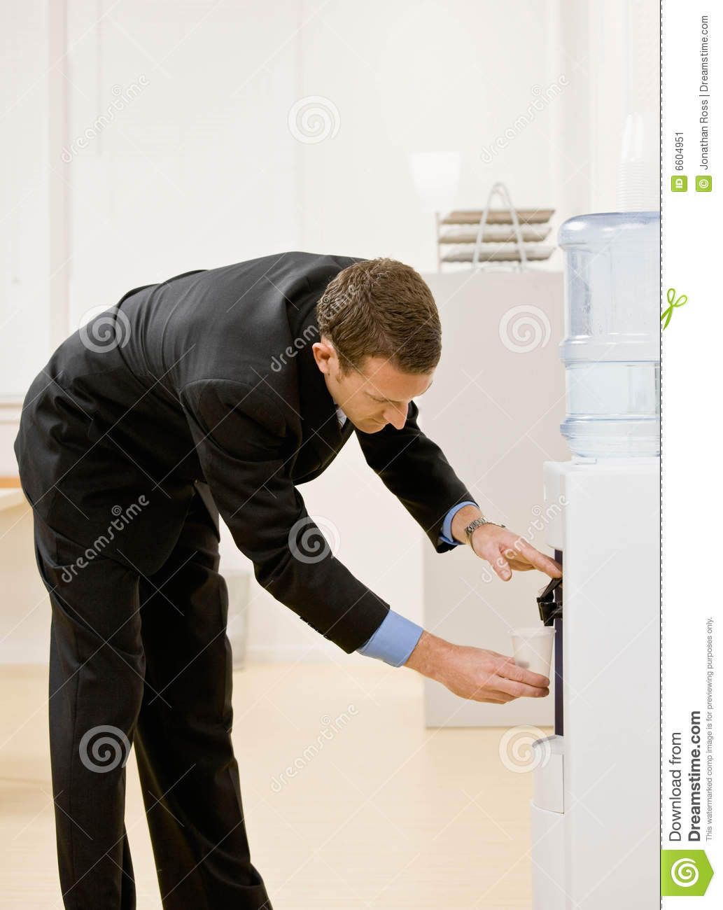 Business man gets water from water cooler
