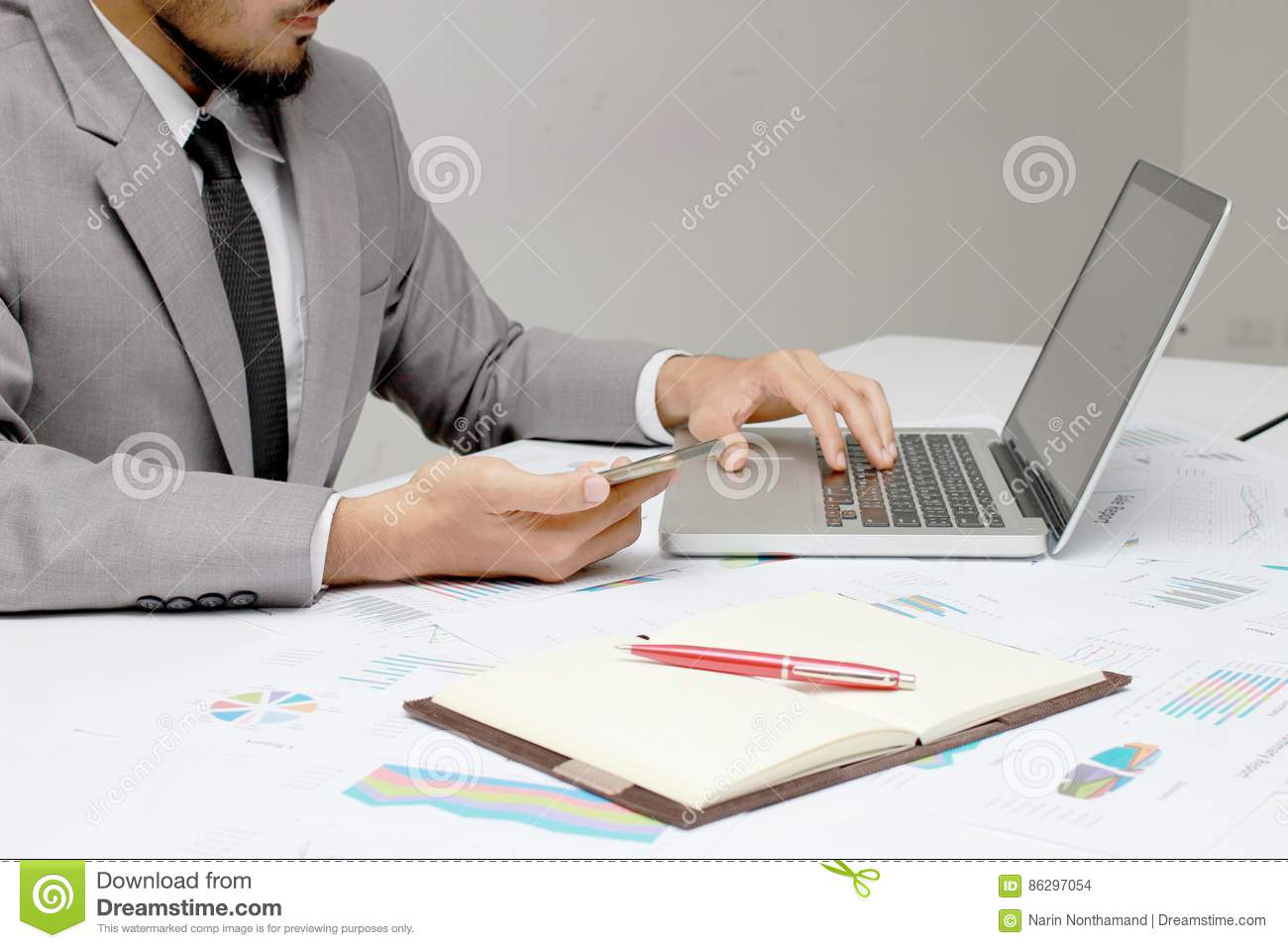 Business man hands busy using cell phone, laptop, pen and notebook at office desk. Analysis the charts and graphs showing the resu