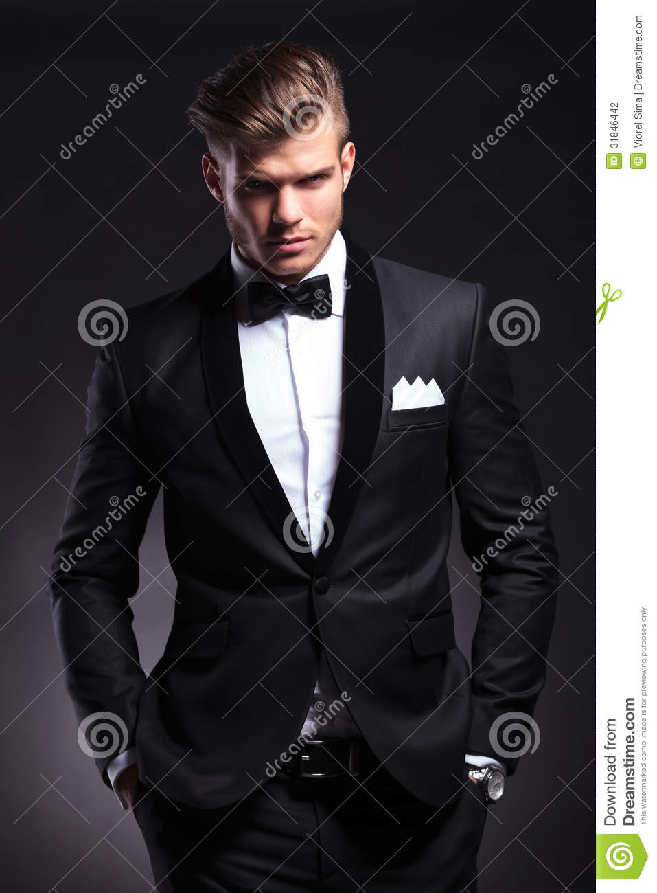 Business man holds both hands in pockets