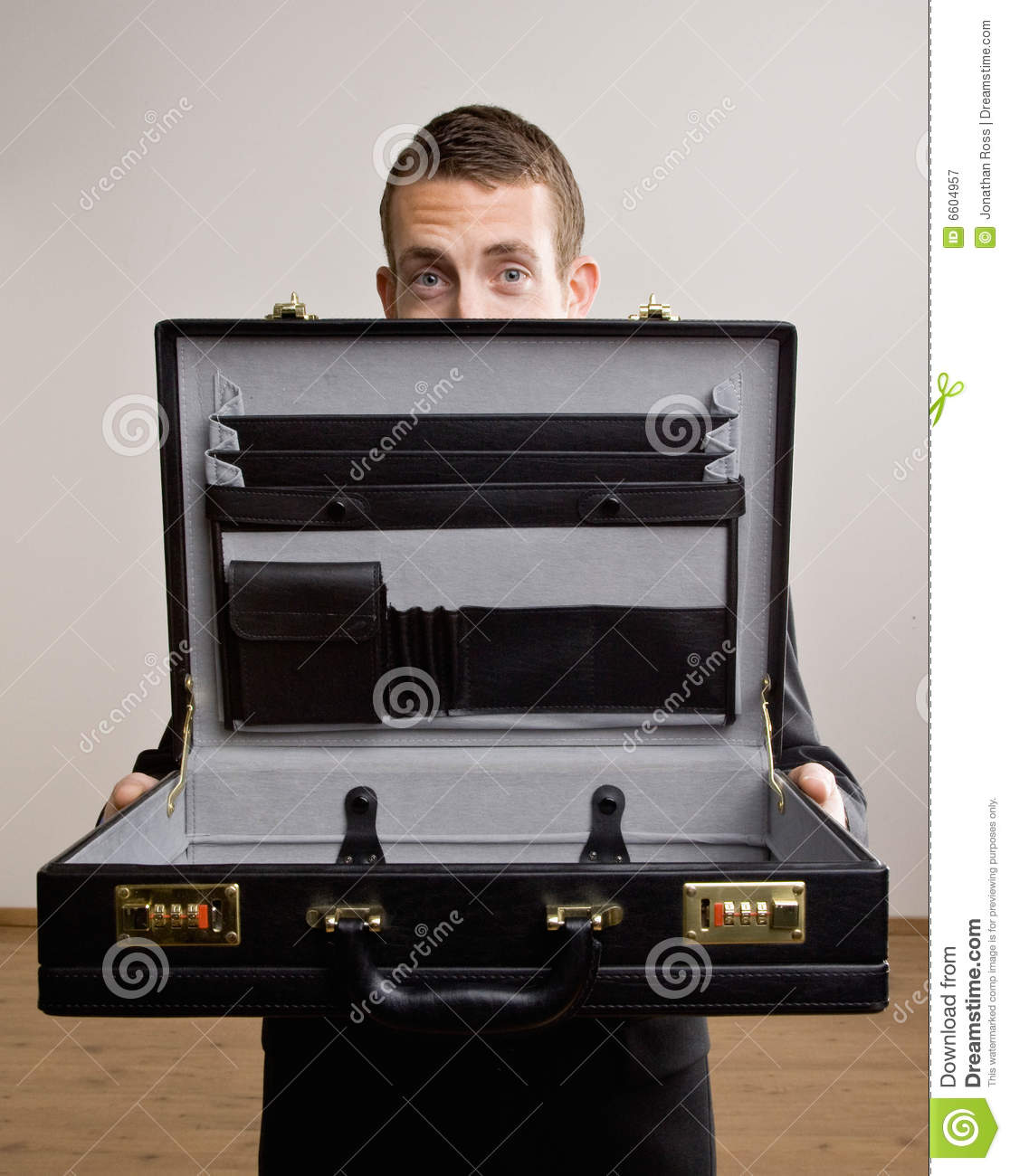 Business man holds up empty brief case