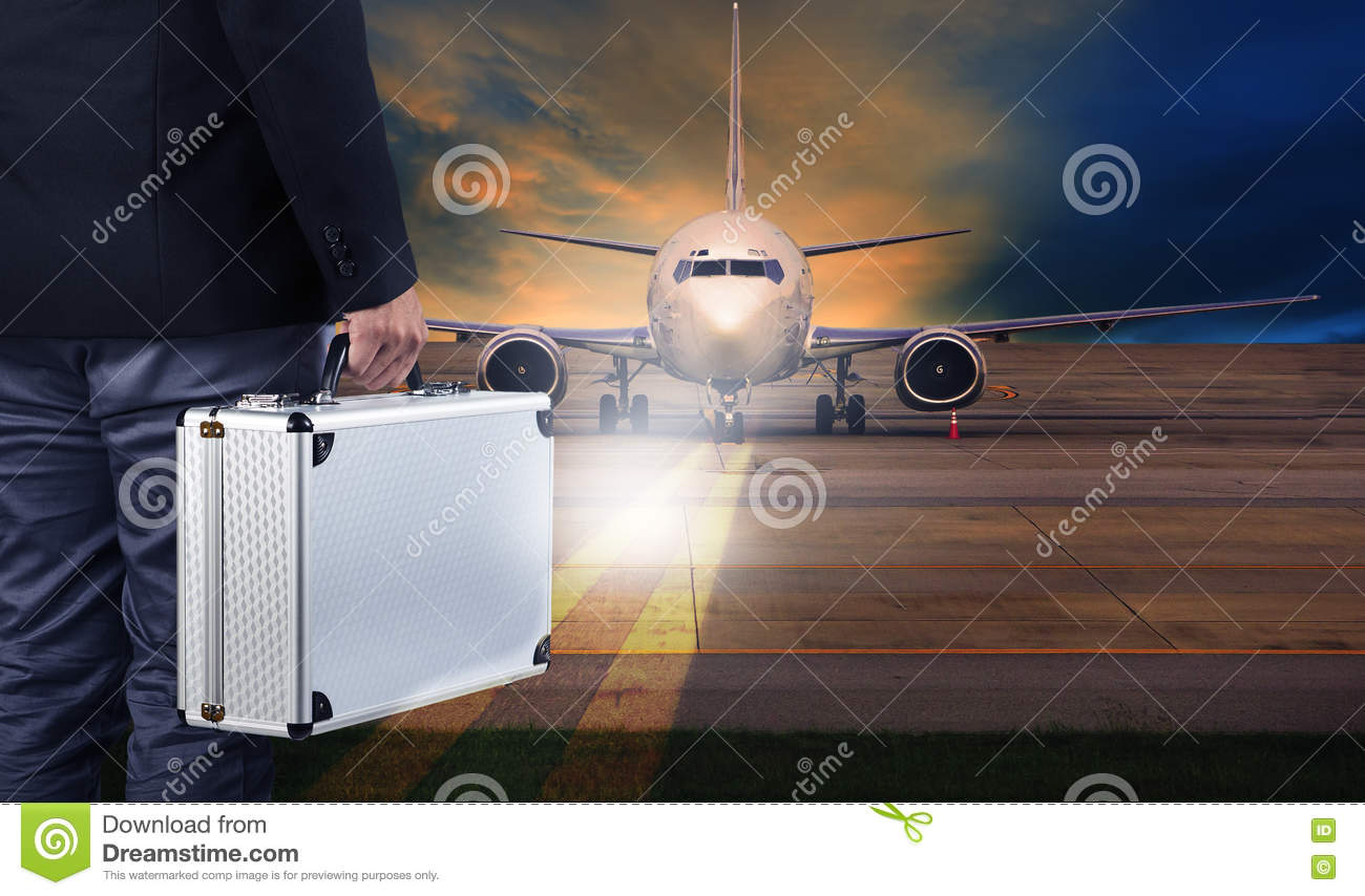 business man with metal strong luggage standing in airport runways and air plane preparing to departure
