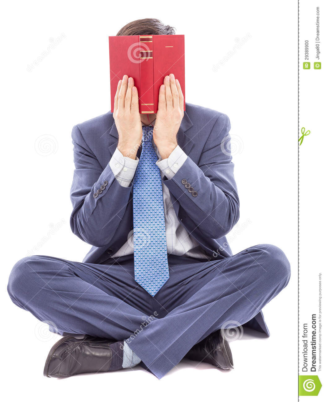 Book Covering Face : Business man sitting cross legged covering his face with a
