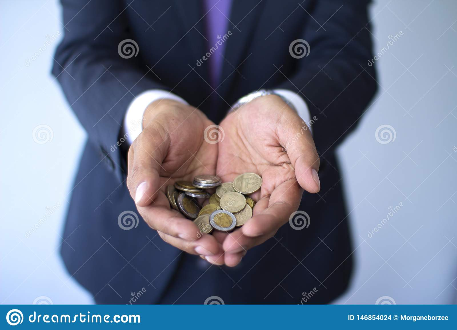 Business man in a suit holding Peruvian coins, Nuevos Soles currency concept