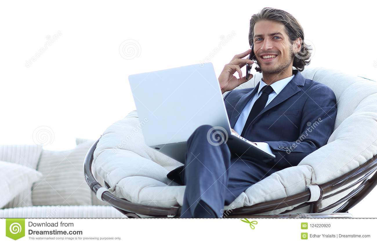 Business man talking on a smartphone sitting in the living room