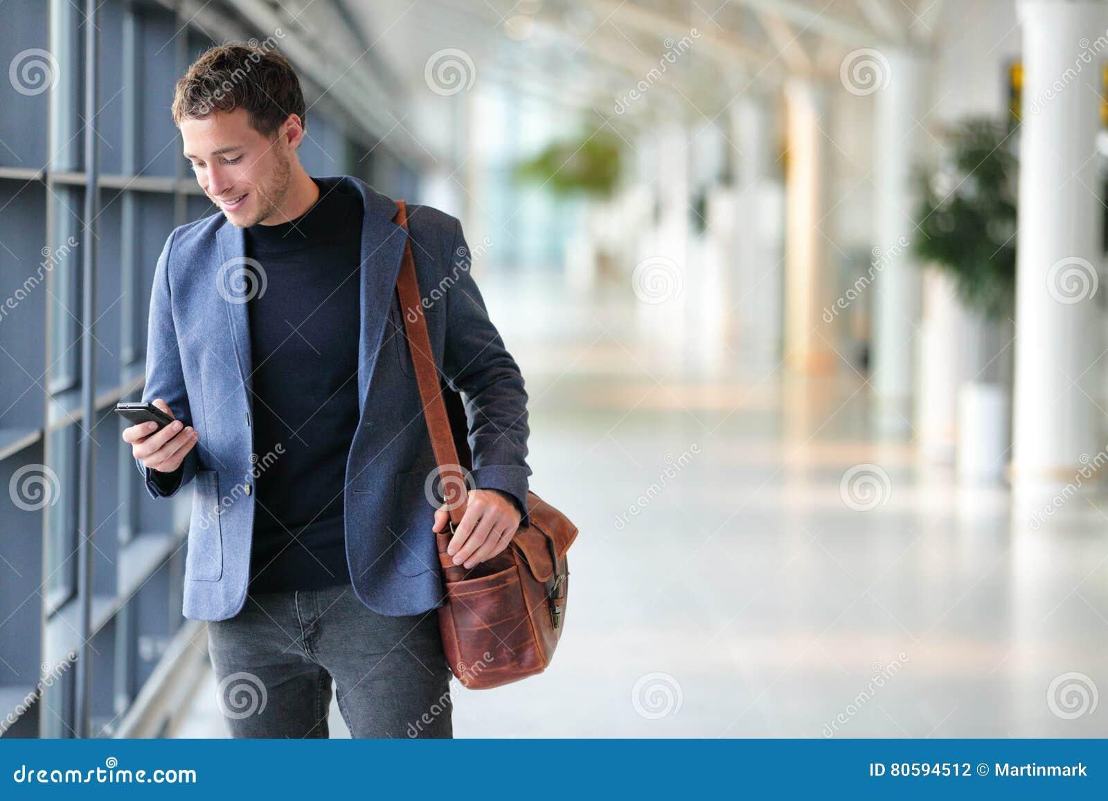 Business man using mobile phone app in airport
