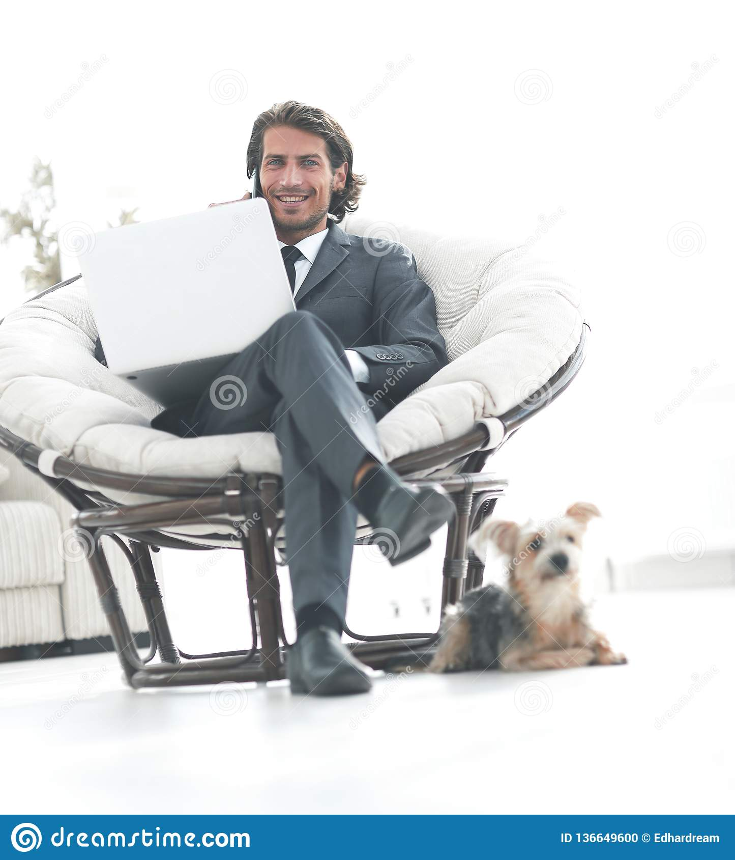 Successful business man working on a laptop and talking on a smartphone