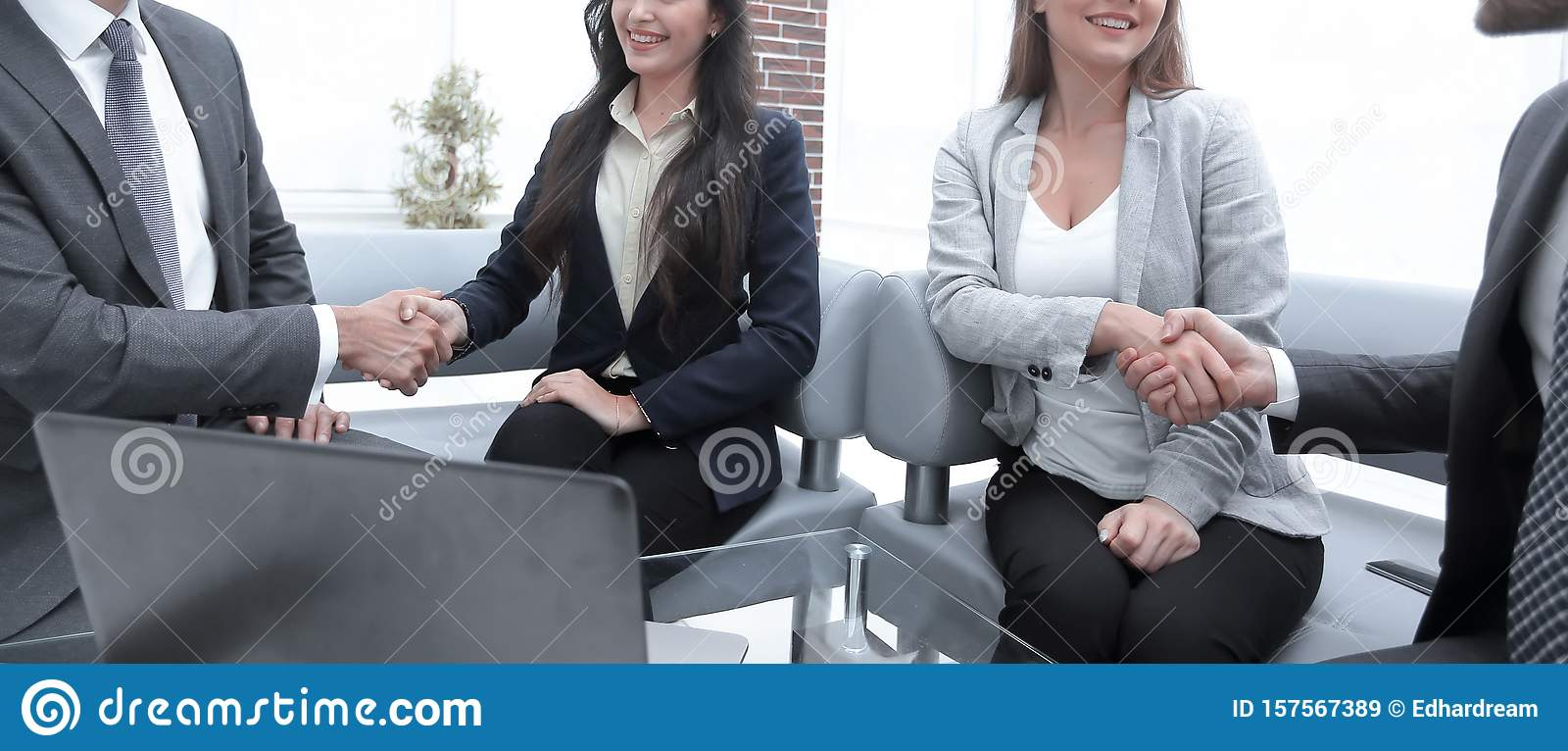 Business associates shaking hands in office.