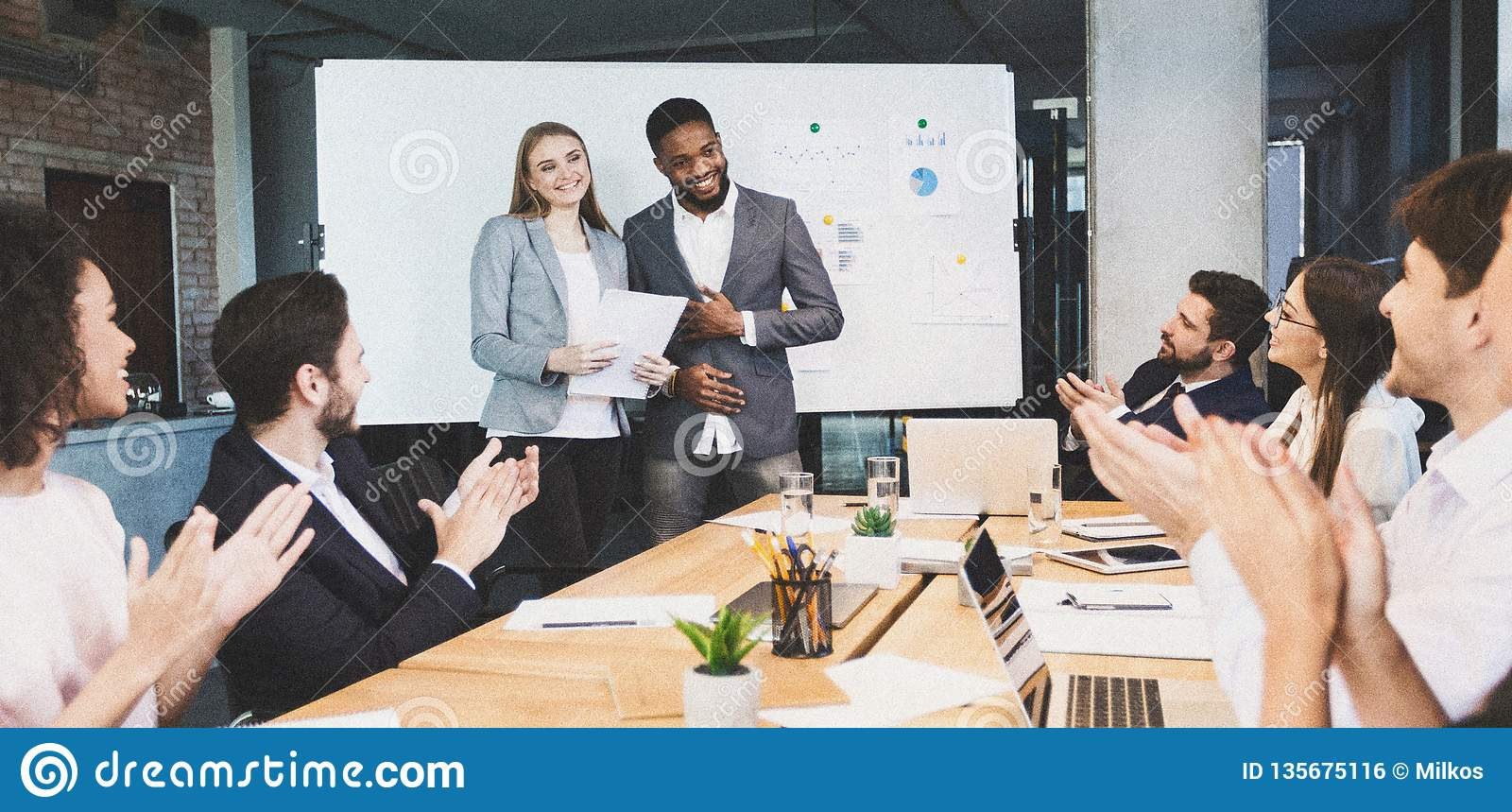 Business partners prising co-workers for presentation