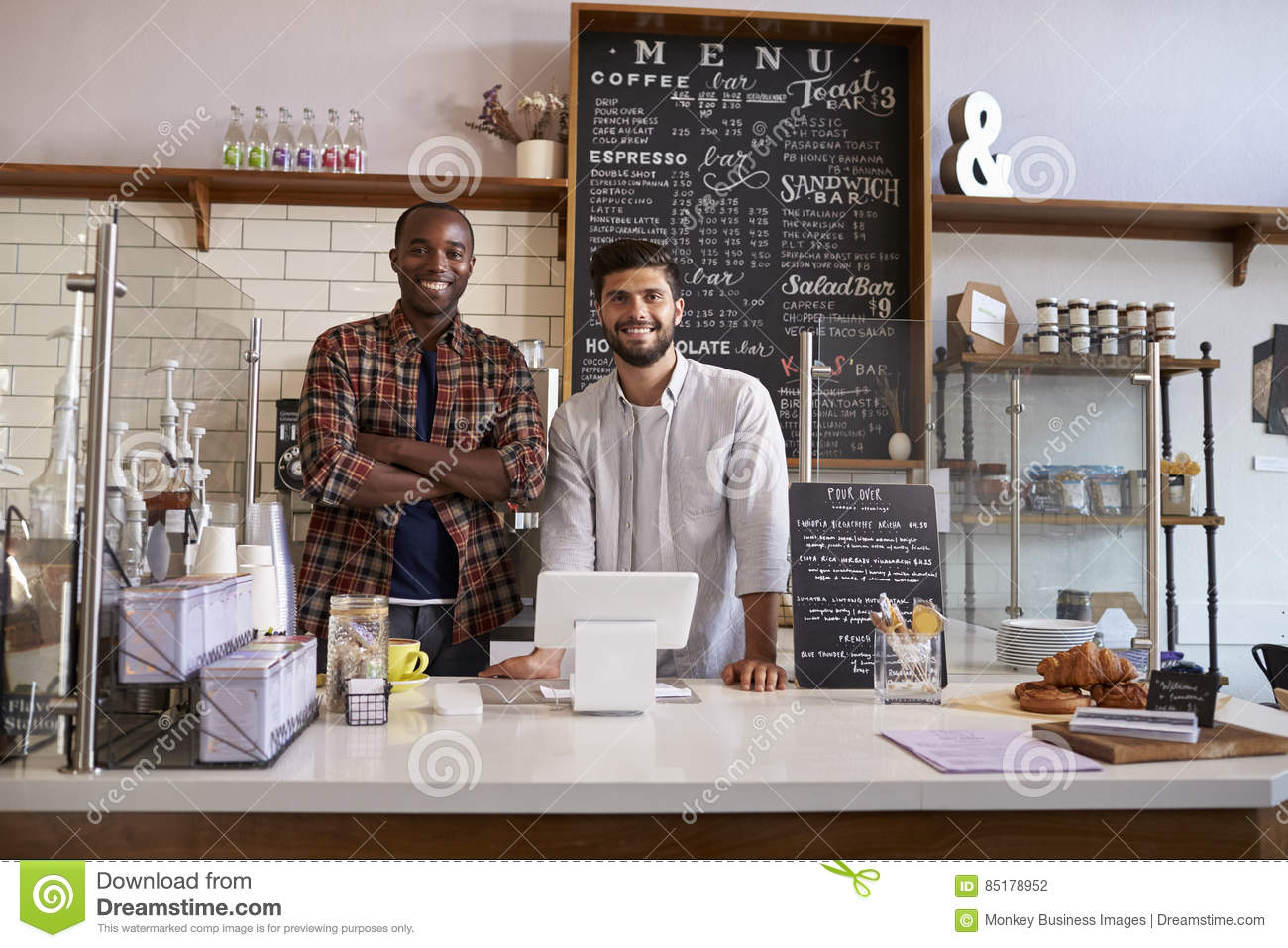 Business partners stand behind the counter at a coffee shop